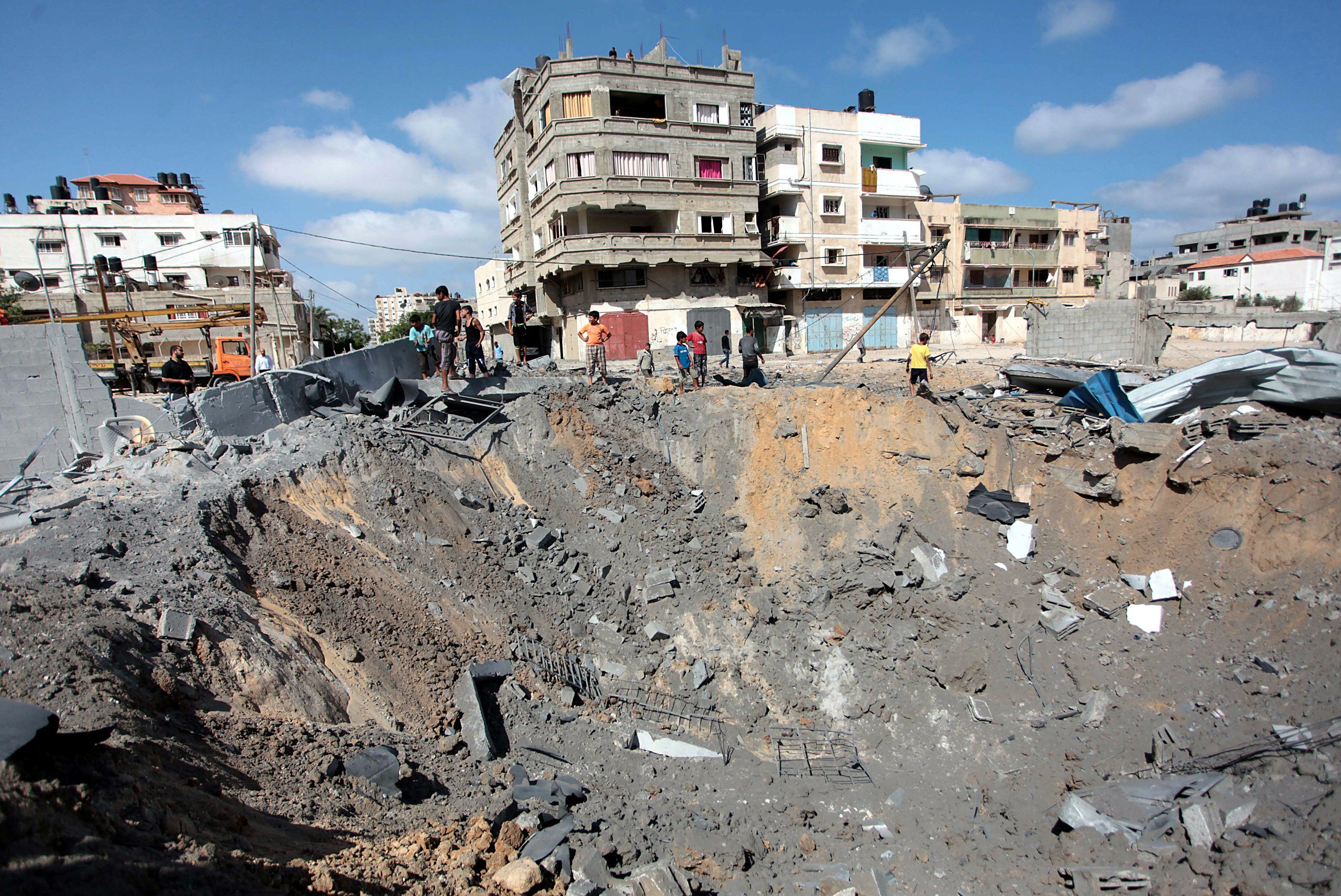 Palestinians inspect damaged areas following an overnight Israeli air strike, on July 3, 2014 in Gaza City, Gaza.
