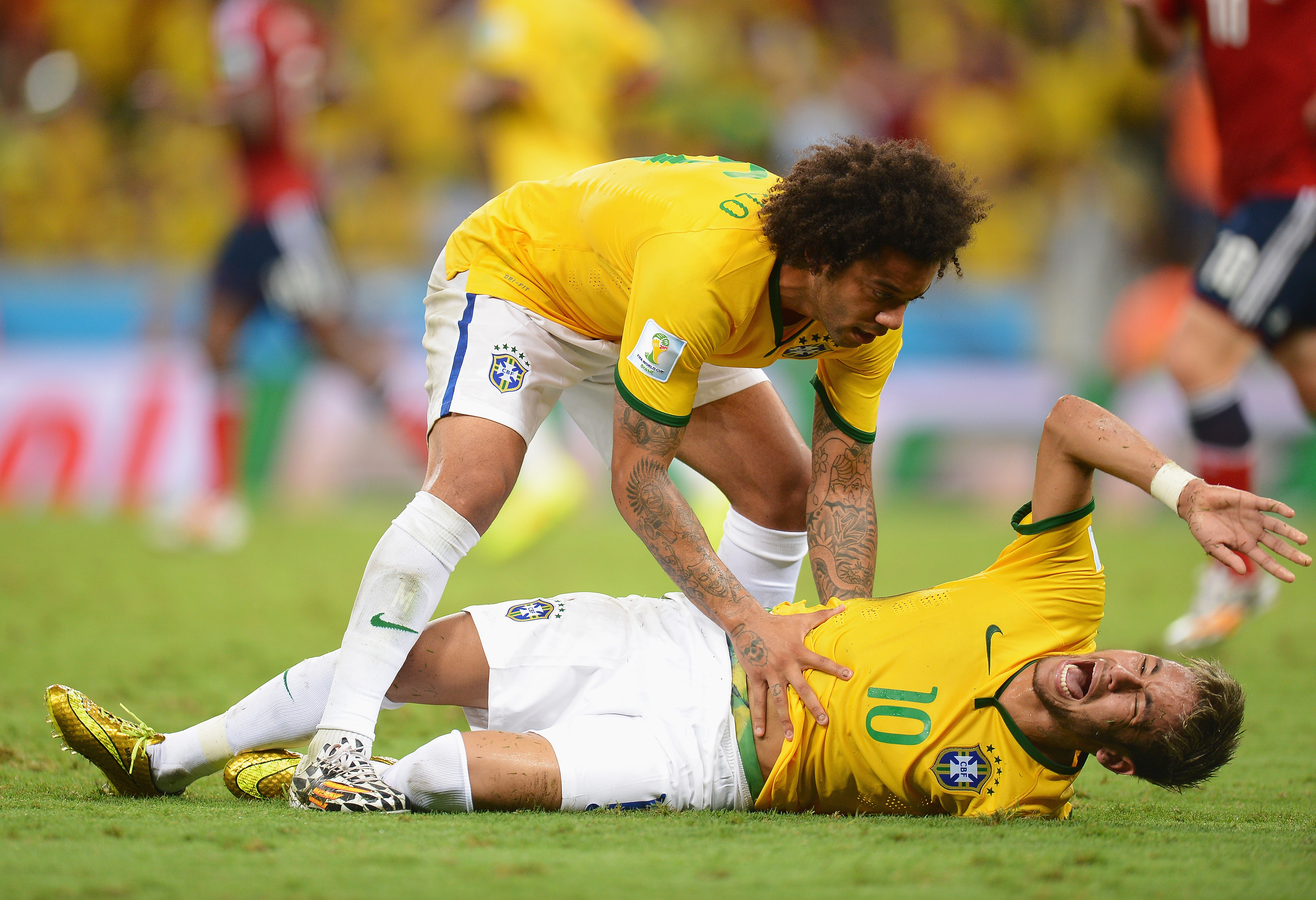 Neymar lies injured while Marcelo shows concern looking over him during the 2014 FIFA World Cup Brazil Quarter Final match between Brazil and Colombia at Estadio Castelao in Fortaleza, Brazil on July 4, 2014.