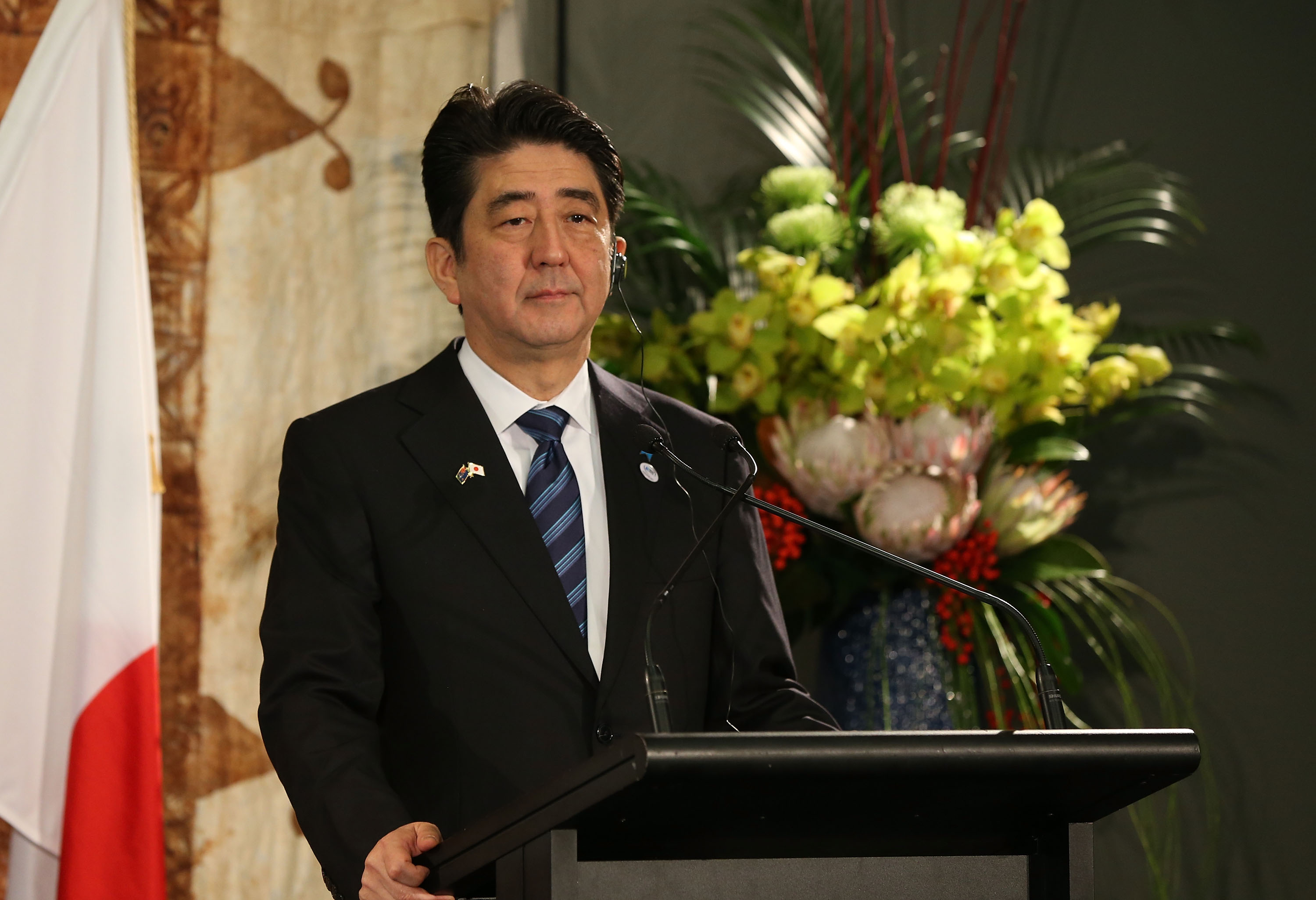 Japanese Prime Minister Shinzo Abe speaks to the media after a traditional Maori welcome at Government House and talks with New Zealand Prime Minister John Key on July 7, 2014, in Auckland.
