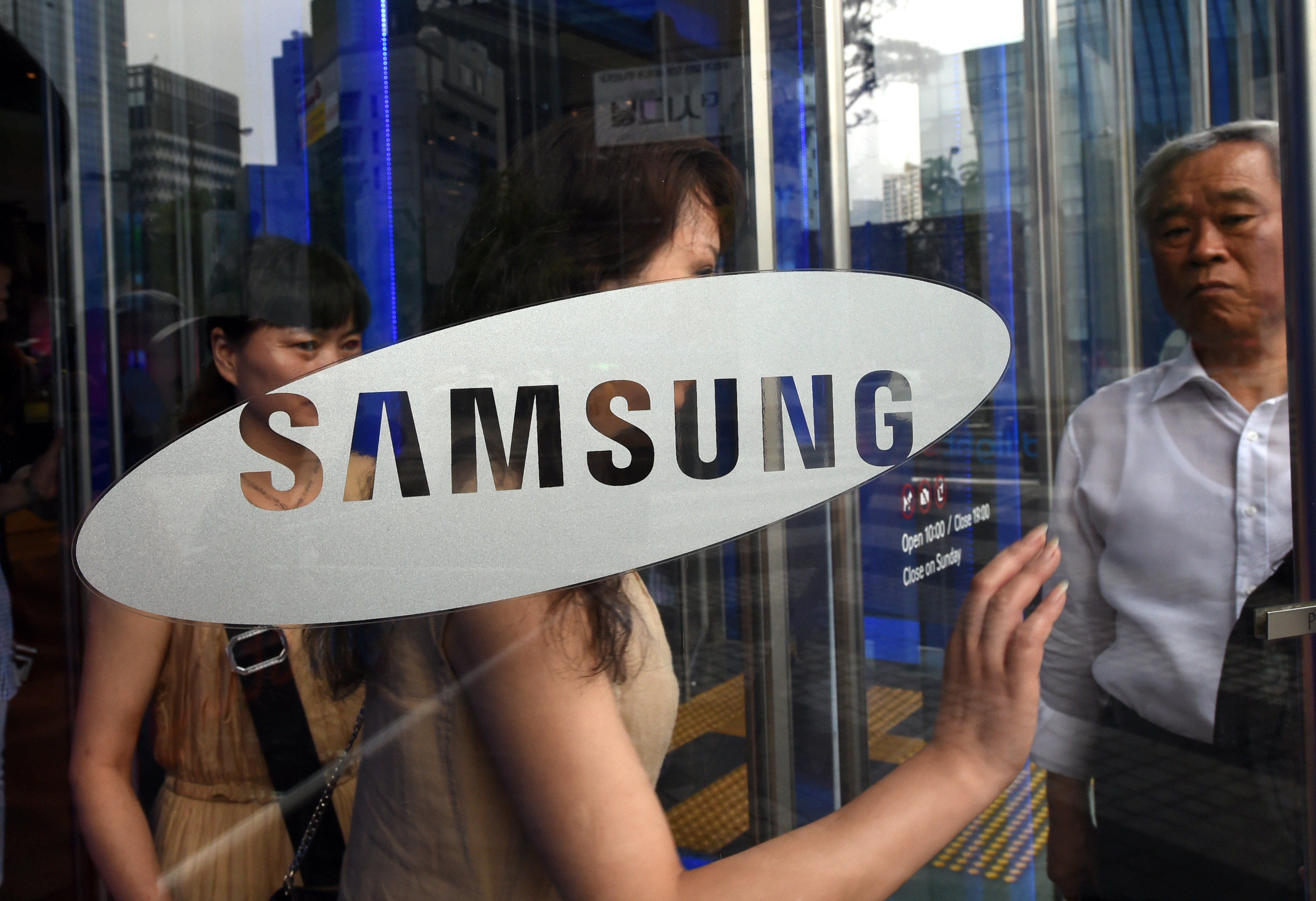 Visitors walk past a glass door showing the logo of Samsung Electronics at the company's showroom in Seoul on July 8, 2014.