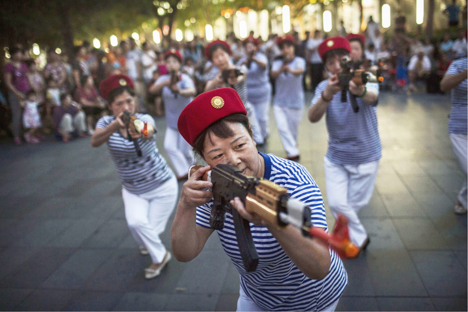 Jul. 8, 2014. Chinese women hold plastic guns as they take part in a performance by an amateur dance troupe re-enacting musical theatre scenes of the anti-Japanese war of 1937-1945 at a mall in Beijing, China.