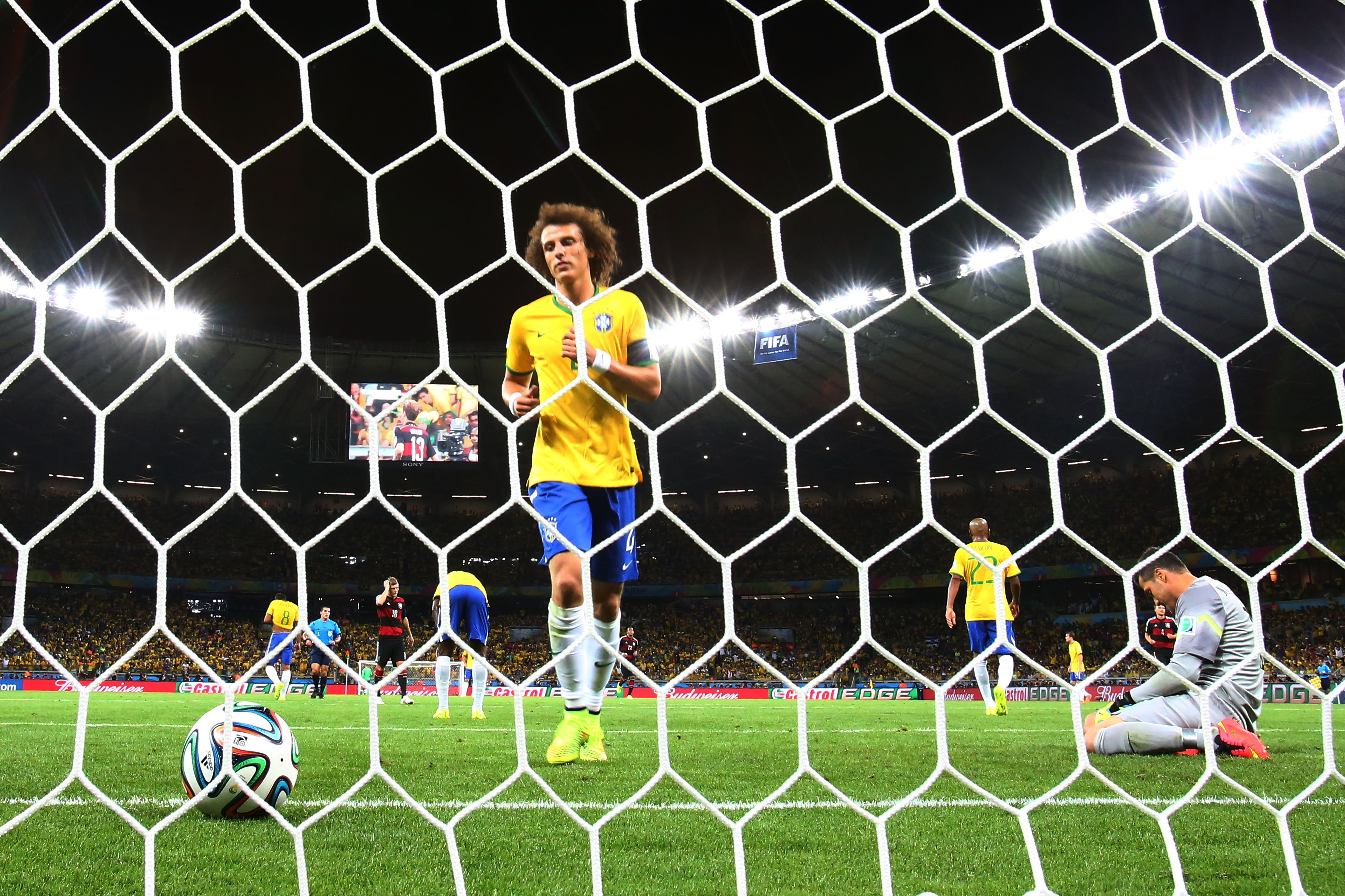 David Luiz of Brazil retrieves the ball from the net after Germany's sixth goal scored by Andre Schuerrle past goalkeeper Julio Cesar of Brazil at Estadio Mineirao on July 8, 2014 in Belo Horizonte, Brazil.