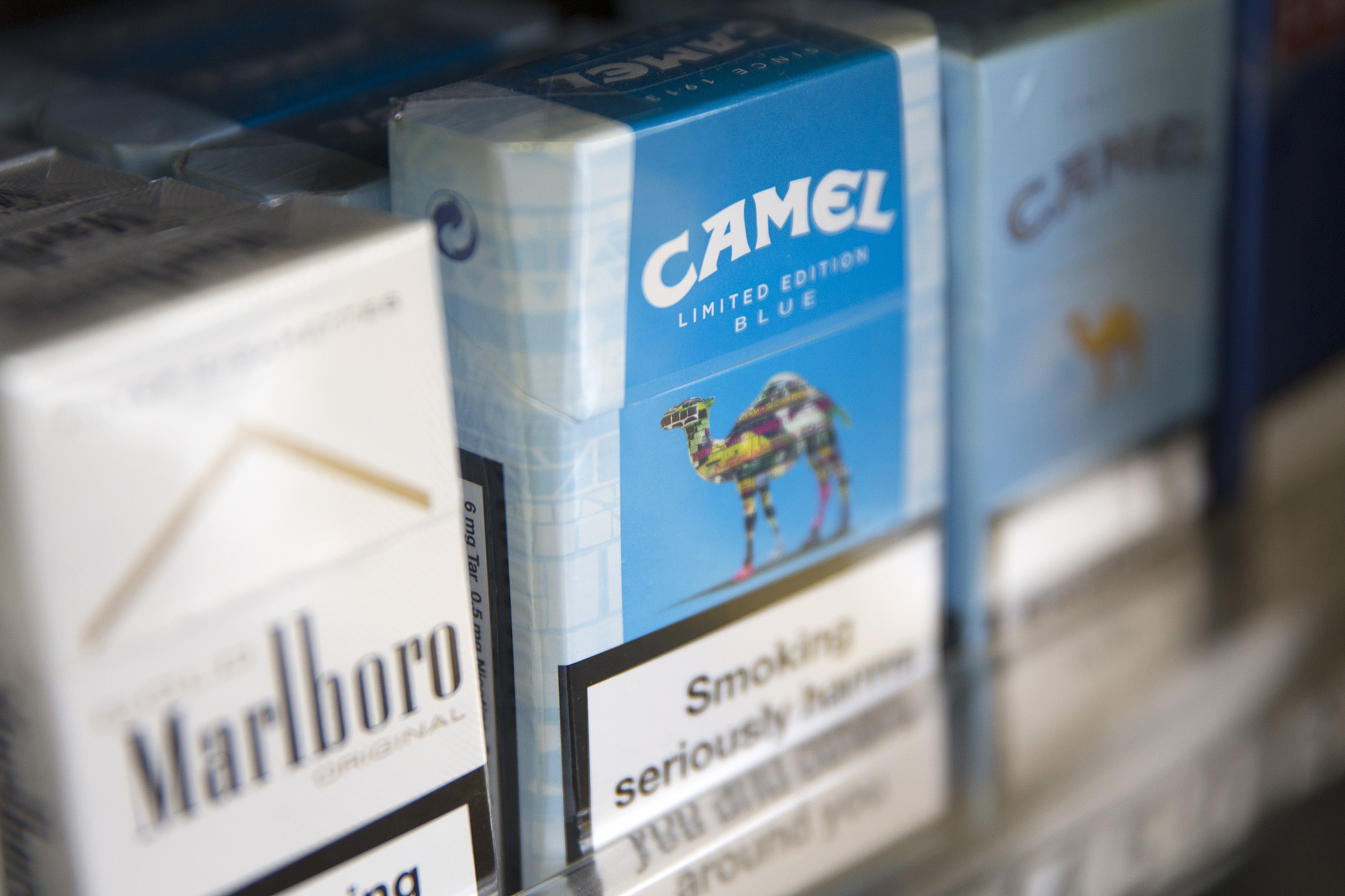 Packs of Camel cigarettes, manufactured by Reynolds American Inc., in a display rack in London on July 11, 2014.