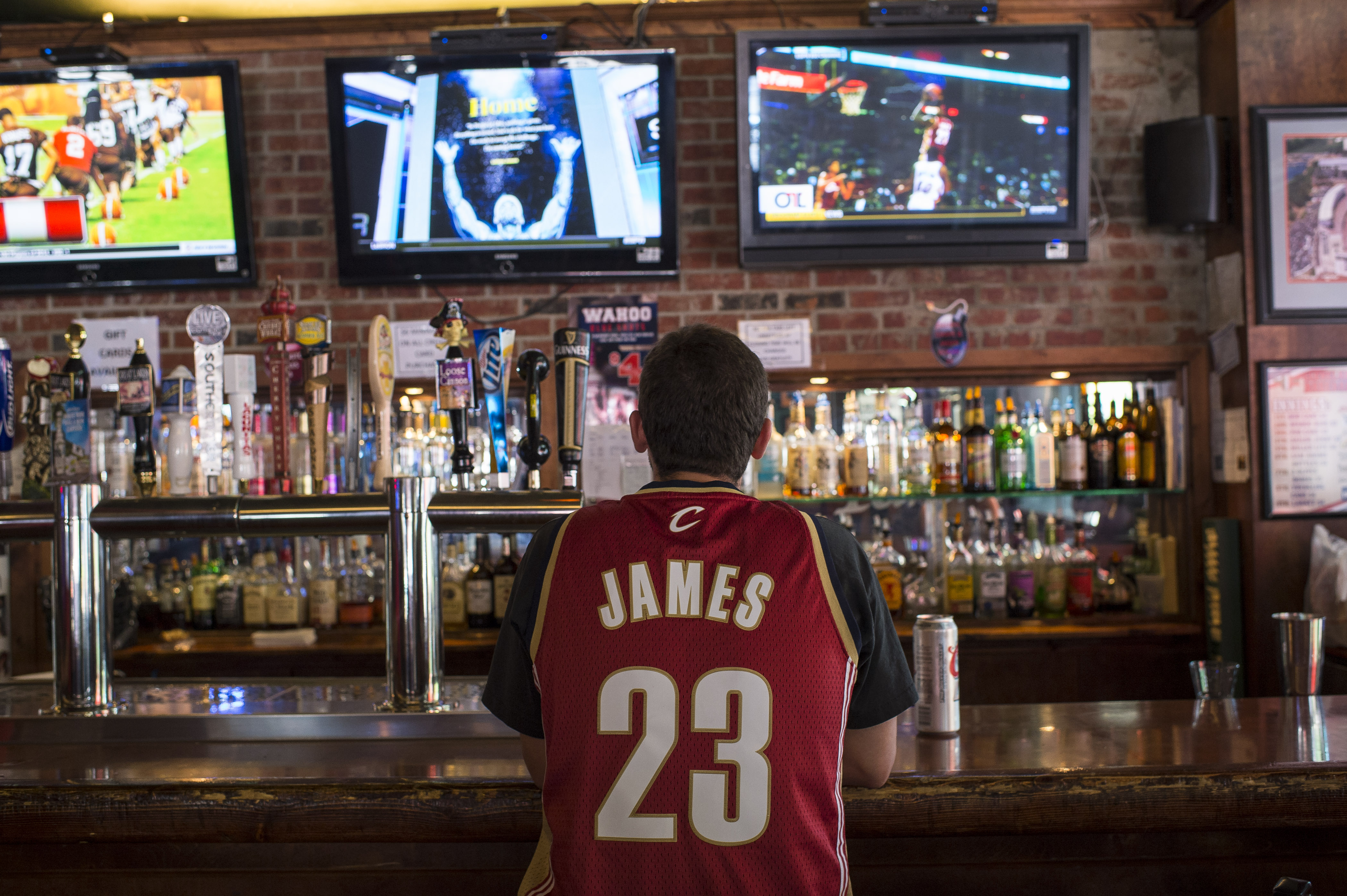 A Cleveland Cavaliers fan watches news coverage of LeBron James' return at Panini's Bar and Grille in downtown Cleveland on July 11, 2014