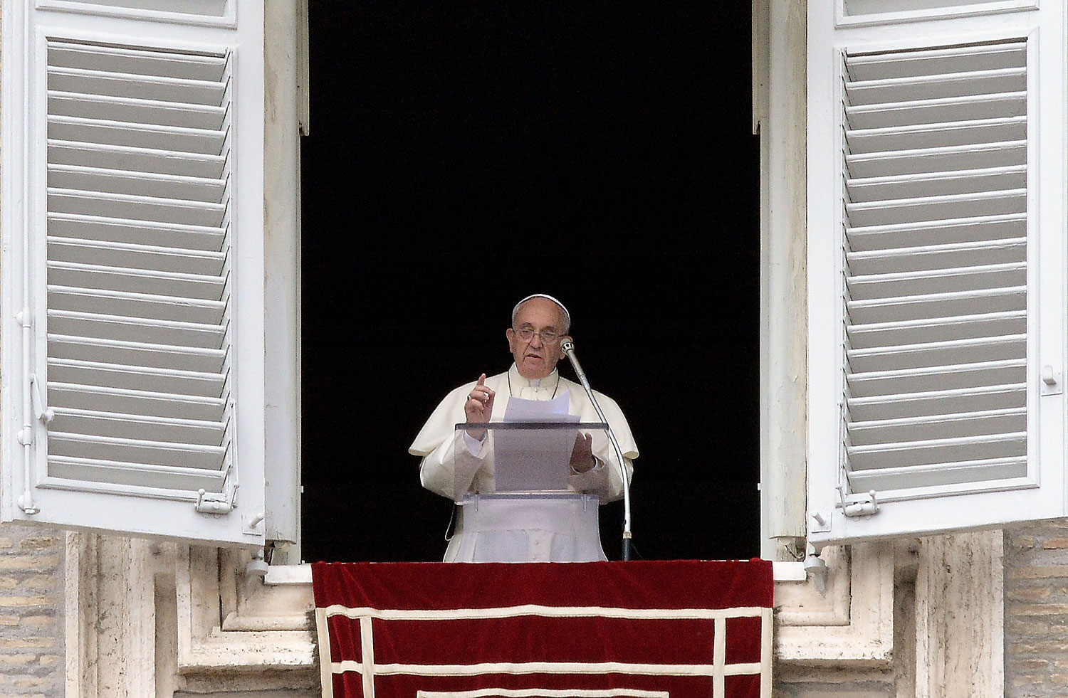 Pope Francis addresses faithful from the window of his study overlooking St. Peter's Square at the Vatican during his Sunday Angelus prayer on July 13, 2014