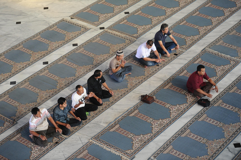 Muslims pray before breaking of the fast during Ramadan on July 13, 2014 in Surabaya, Indonesia.