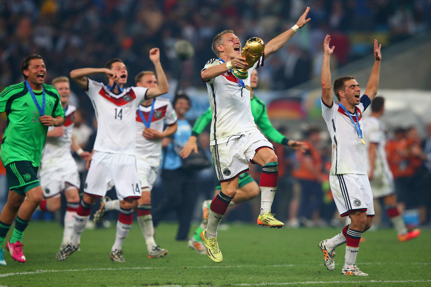 Bastian Schweinsteiger  of Germany and his teammates celebrate with the World Cup trophy  after defeating Argentina 1-0 in extra time during the 2014 FIFA World Cup Brazil Final match between Germany and Argentina at Maracana Stadium in Rio de Janeiro on July 13, 2014.