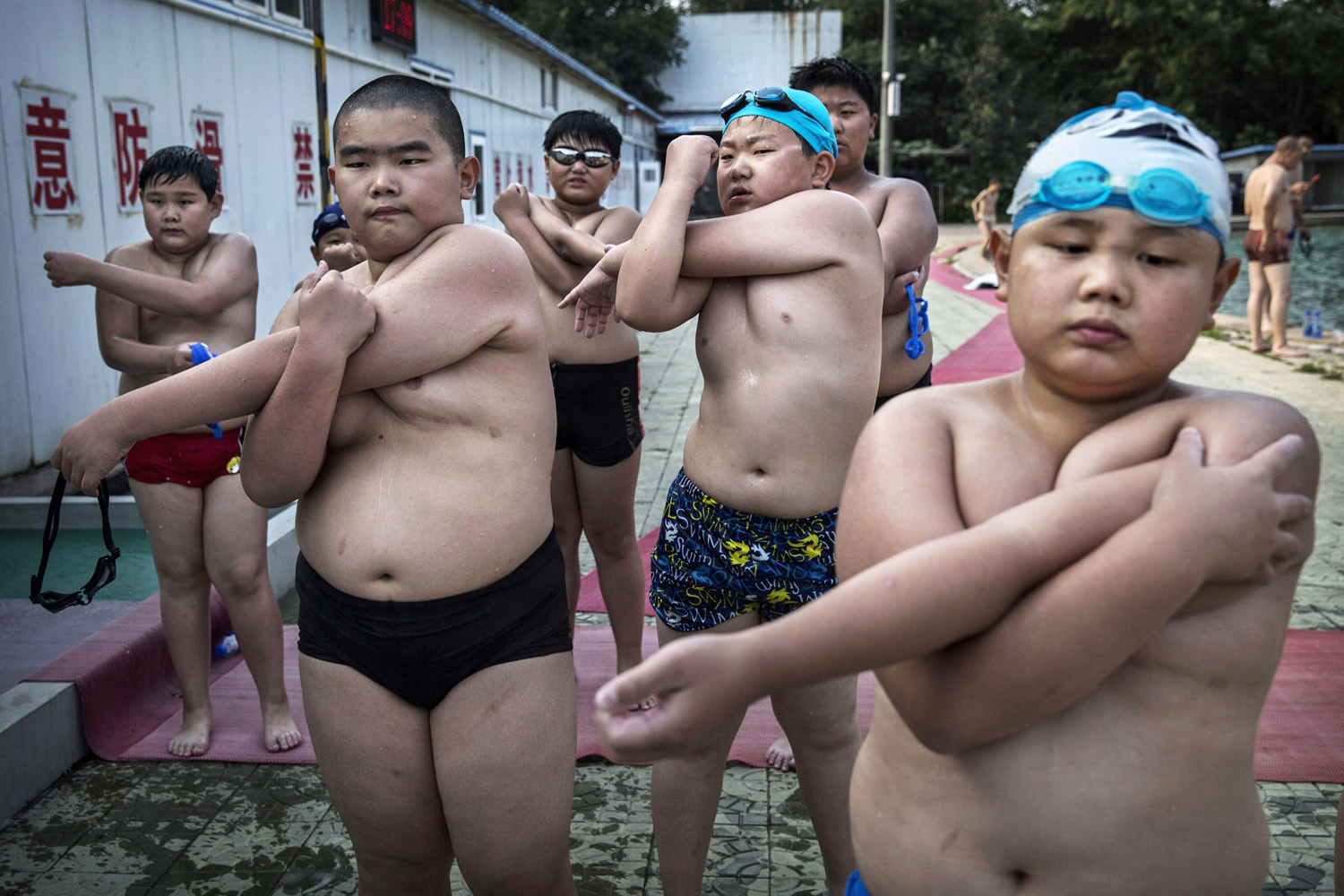 Overweight Chinese students stretch after swimming during training at a camp held for overweight children in Beijing on July 15, 2014.
