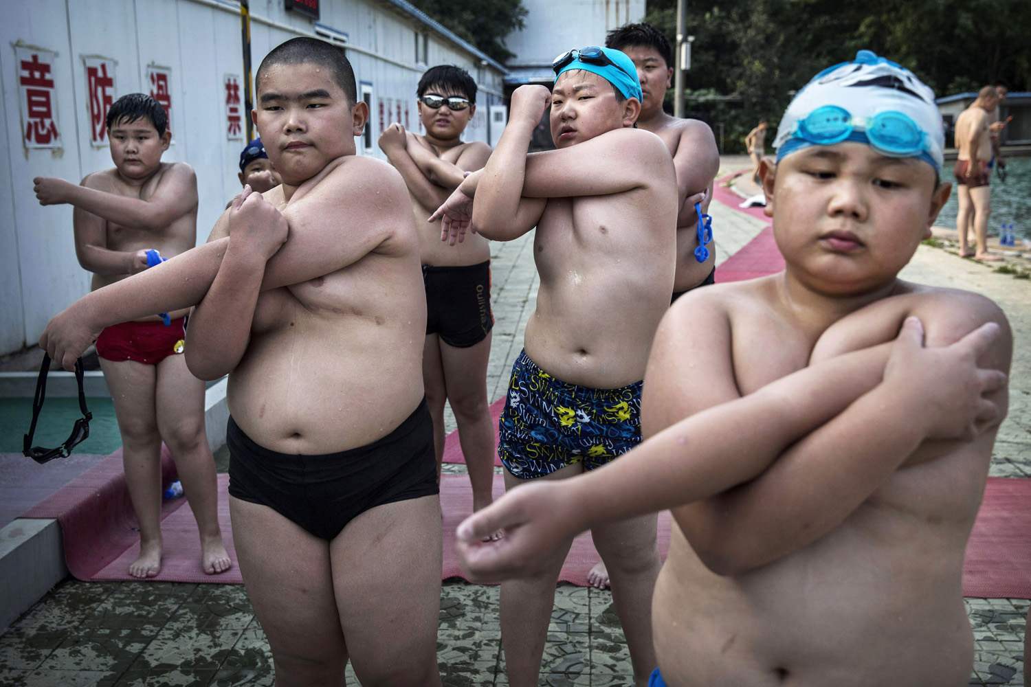 Jul. 15, 2014. Overweight Chinese students stretch after swimming during training at a camp held for overweight children in Beijing, China.