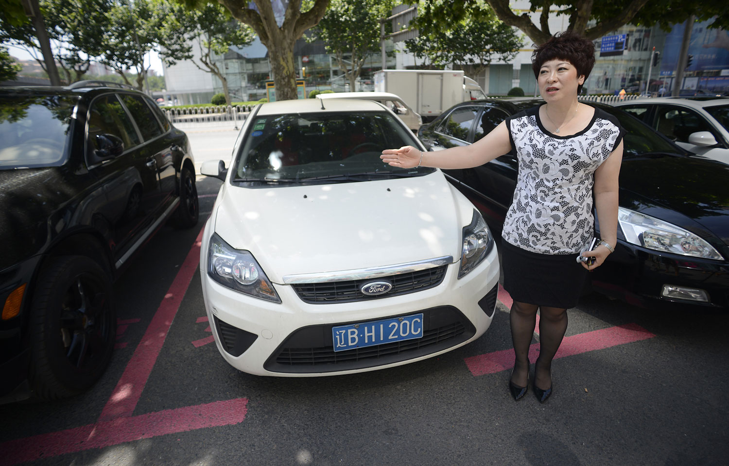 Mall manager Yang Hongjun in front of cars parked in pink spaces in front of the Dashijiedaduhui, or World Metropolis centre, in the seaport city of Dalian, July 7, 2014. The parking spaces are distinctive: marked out in pink, around 30 centimetres wider than normal, and signposted  Respectfully reserved for women .