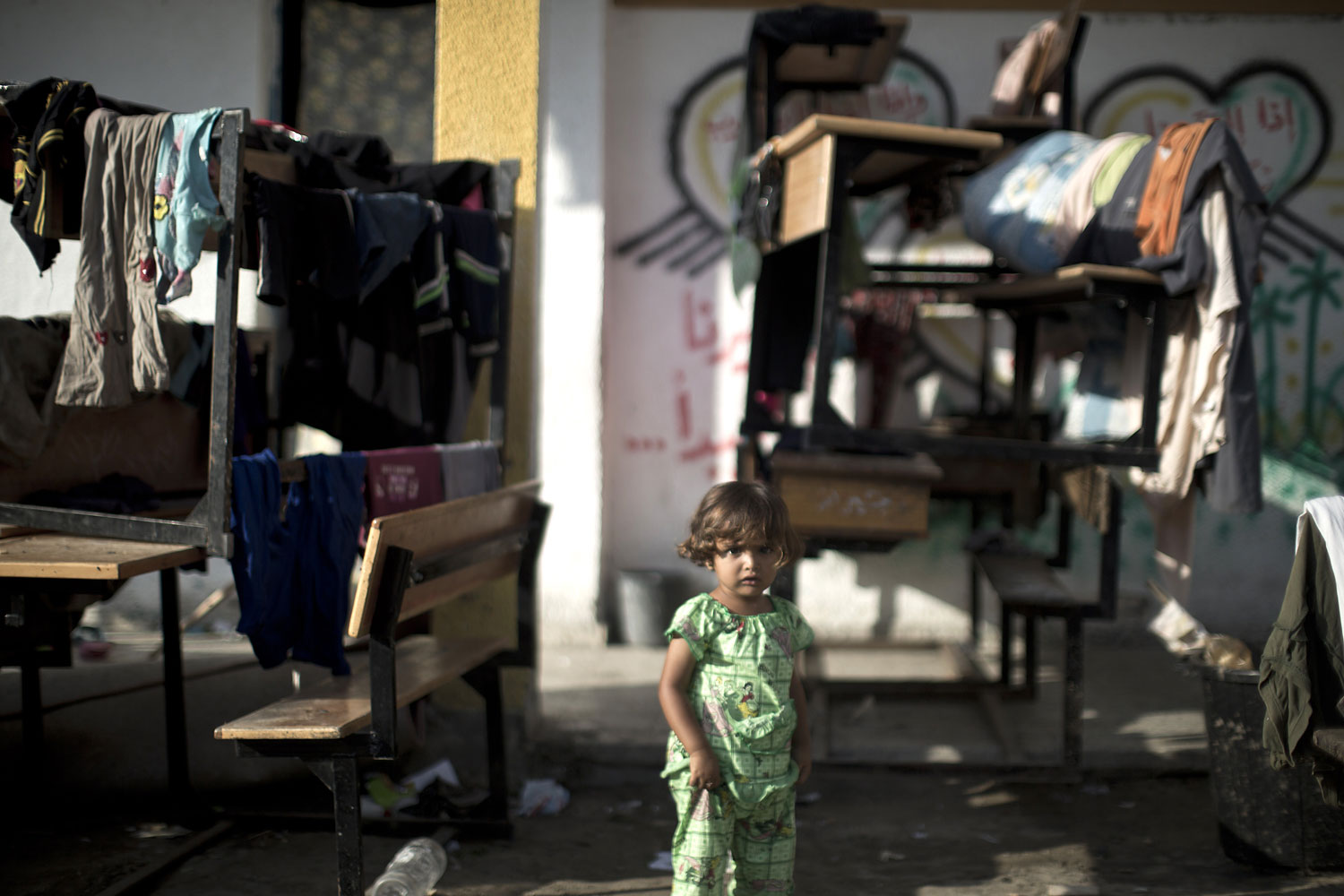 A Palestinian child along with her family, who fled their home during an Israeli ground offensive, take refuge at a UN school in Gaza City with other families, on July 19, 2014.