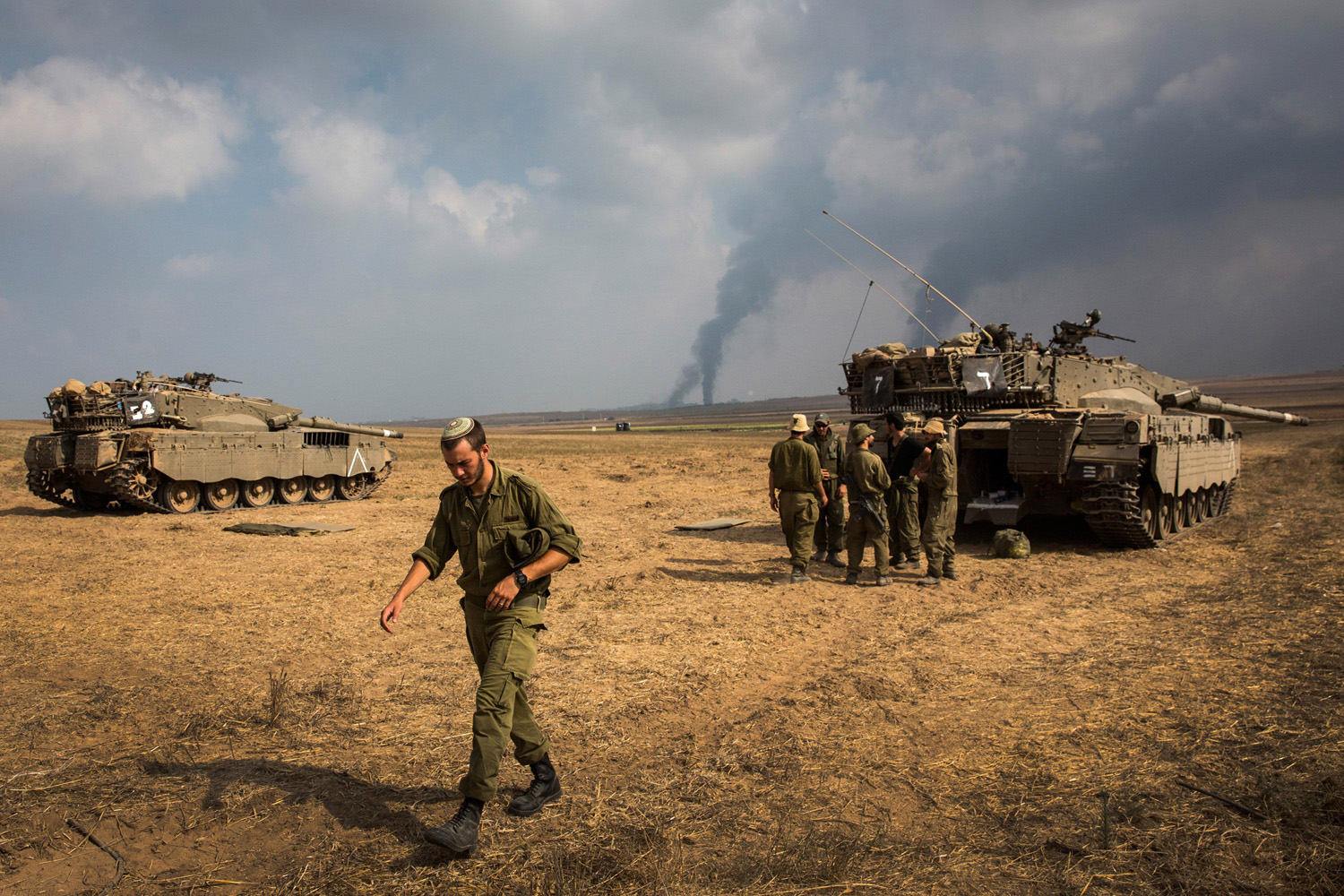 Jul. 22, 2014.  Israeli soldiers stand near their tank while smoke due to airstrikes and shelling rises from Gaza near Sderot, Israel.