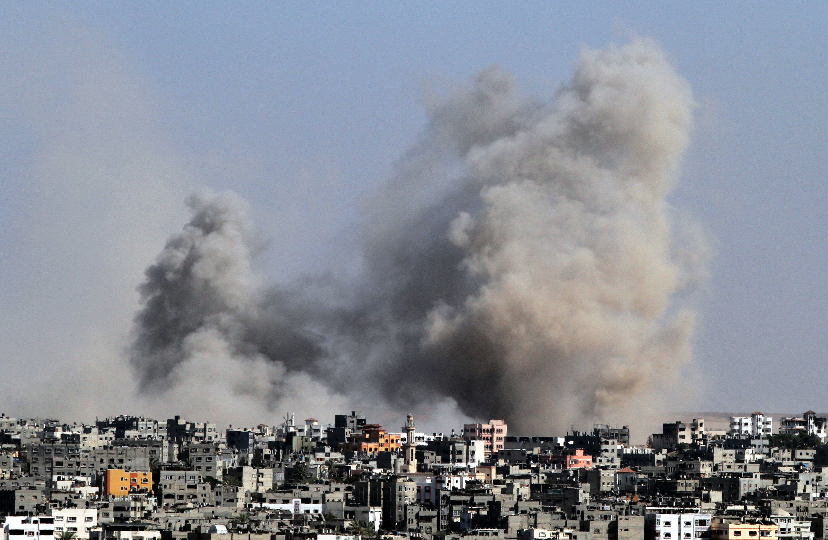 Smoke rises from a building following the Israeli attacks in Gaza City on July 25, 2014.