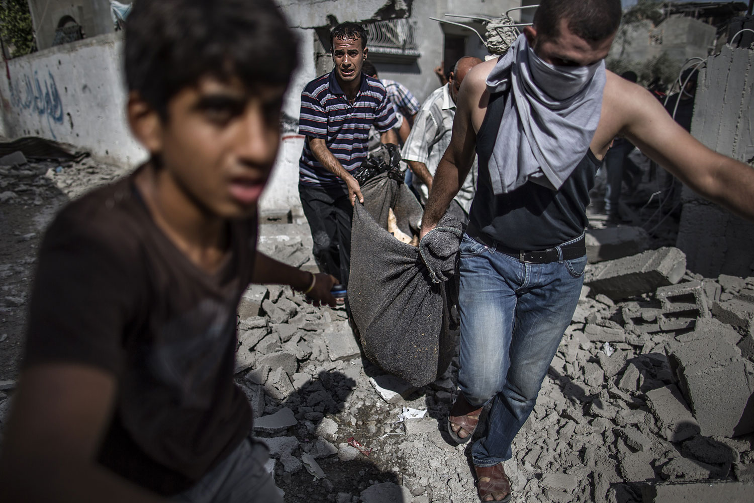 Palestinians recover the body of a man killed when his home was hit the previous night by Israeli fire in the northern district of Beit Hanoun in the Gaza Strip during an humanitarian truce, on July 26, 2014.