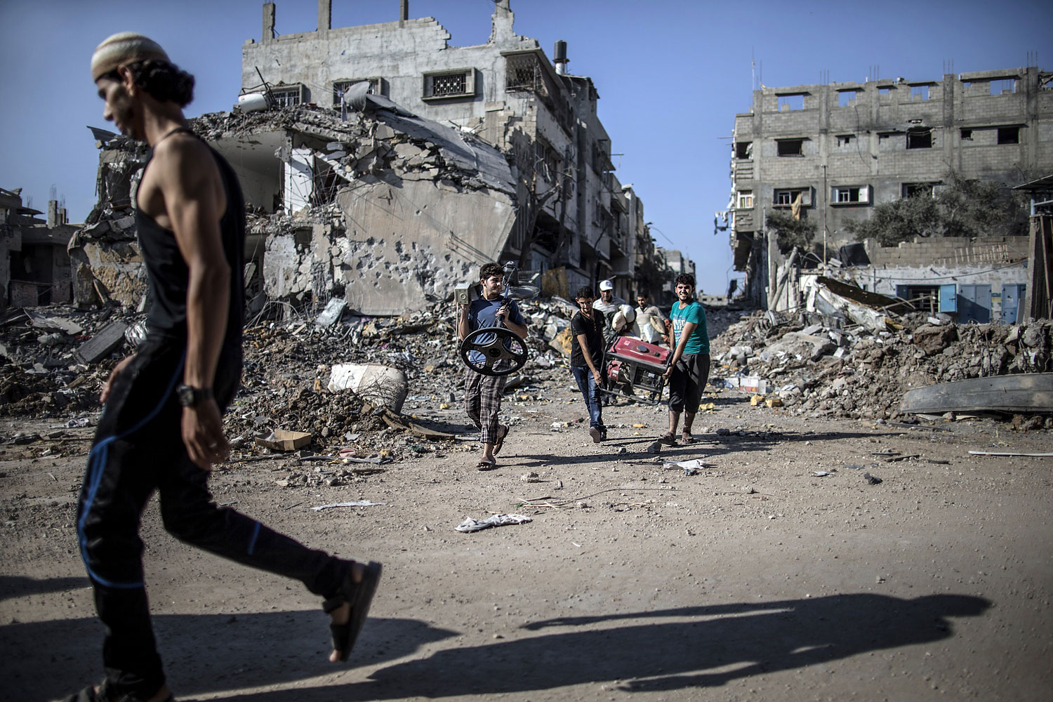 Palestinians carry items and belongings they found in the rubble of destroyed buildings on July 27, 2014 in the Shejaiya residential district of Gaza City as families returned to find their homes ground into rubble by relentless Israeli tank fire and air strikes.