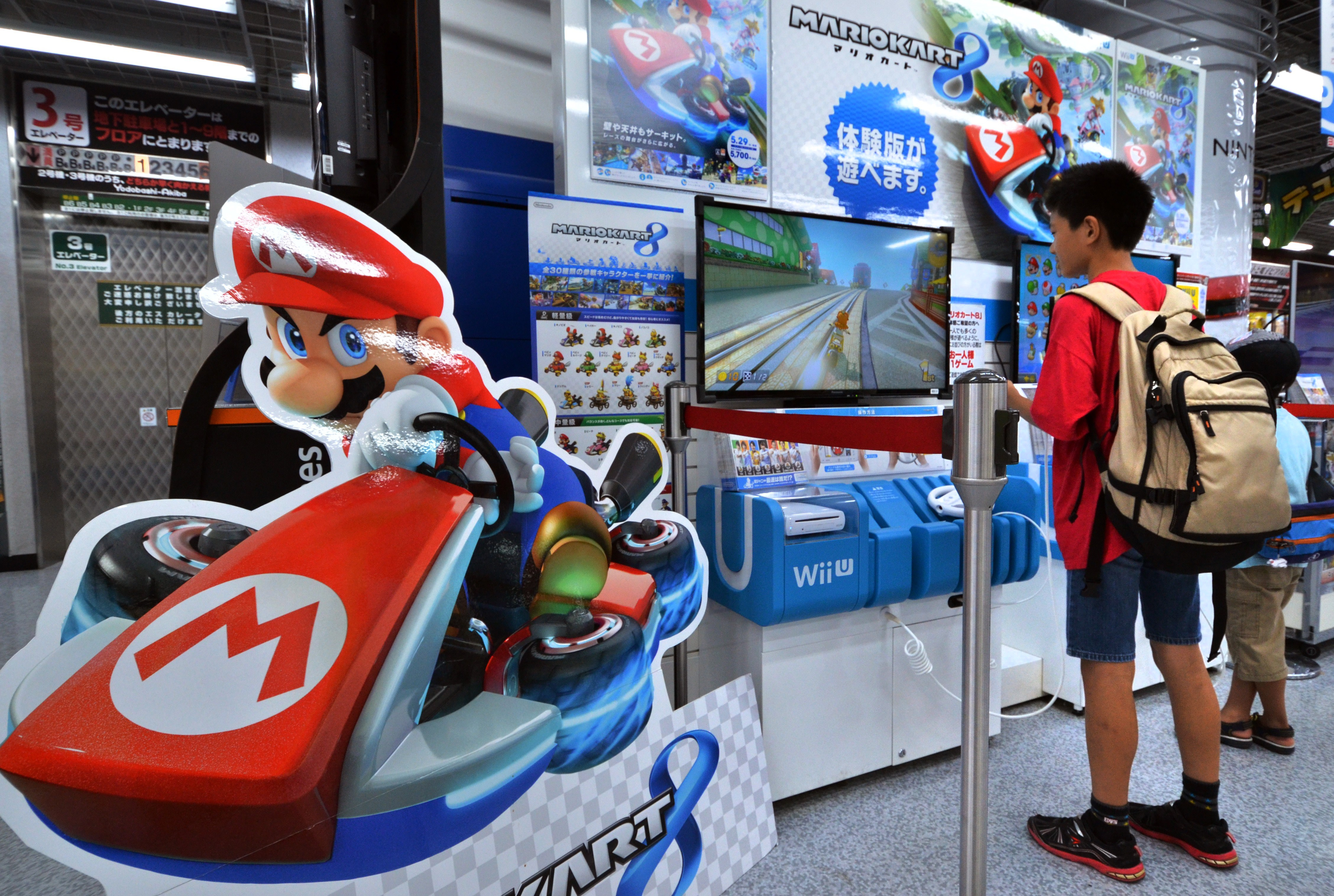 Customers play with Nintendo's videogame console Wii U at an electronics shop in Tokyo on July 30, 2014.
