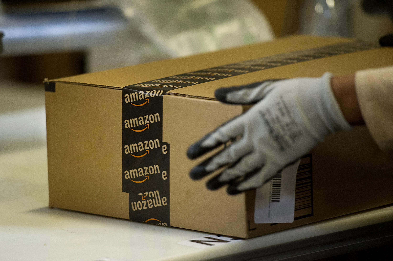 An employee seals a box at the Amazon.com Inc. fulfillment center in Phoenix, Arizona on Dec. 2, 2013.