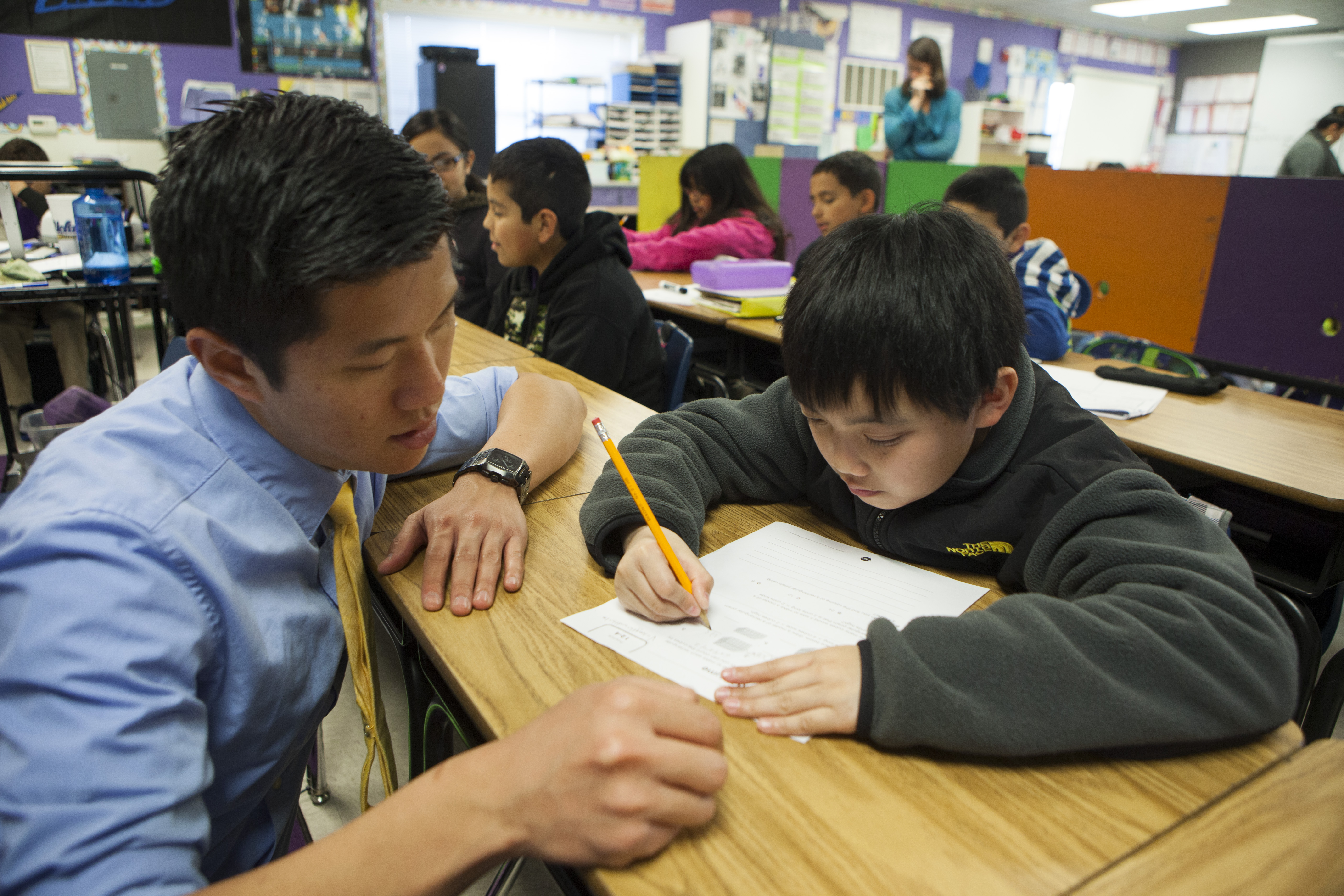 Fifth grade science and math teacher Stephen Pham helps a student at Rocketship SI Se Puede, a charter, public elementary school, on Feb. 18, 2014 in San Jose, California.