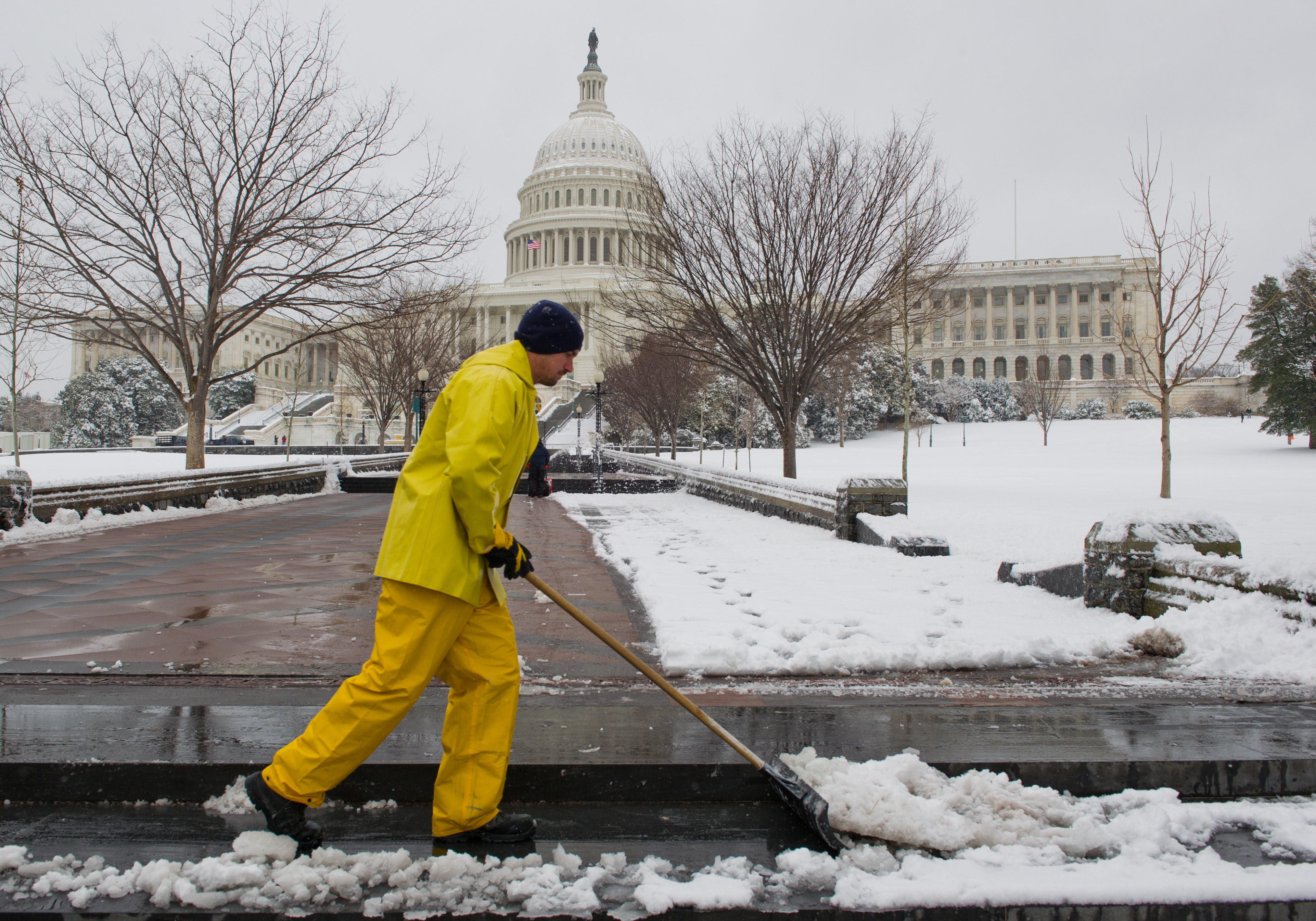 A worker shovels snow from the walkways at the U.S. Capitol in Washington, DC March 17, 2014 the morning after yet another snow storm.