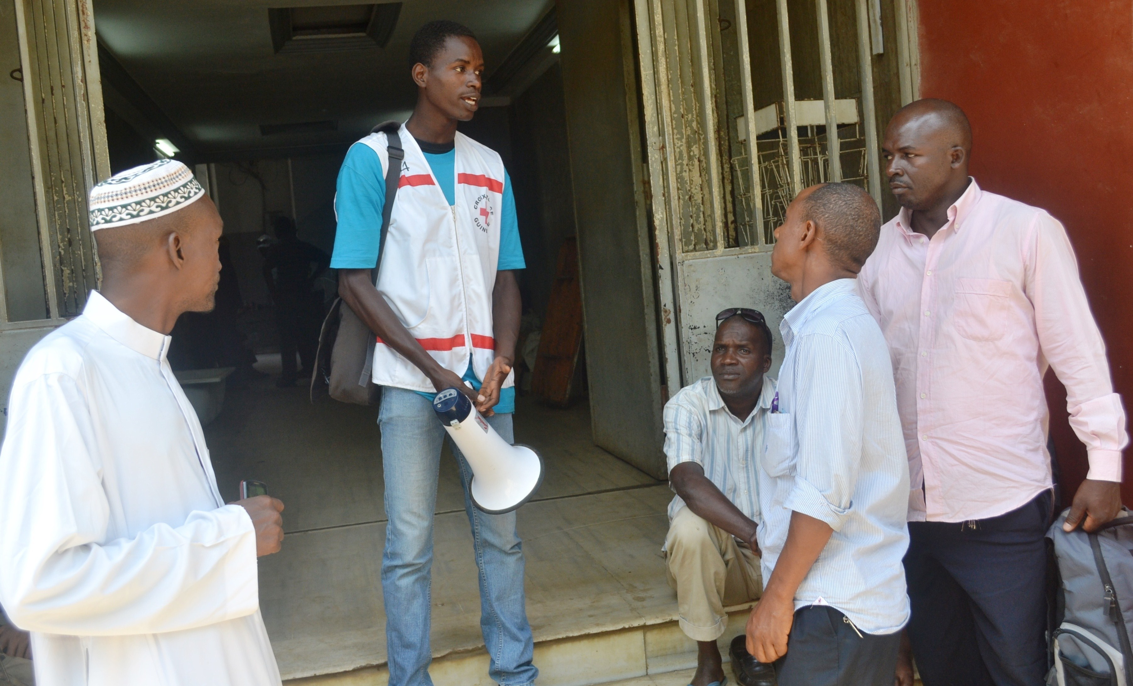 Members of the Red Cross provide information on Ebola to residents in Conakry, Guinea on April 11, 2014 at the start of the largest Ebola outbreak in history