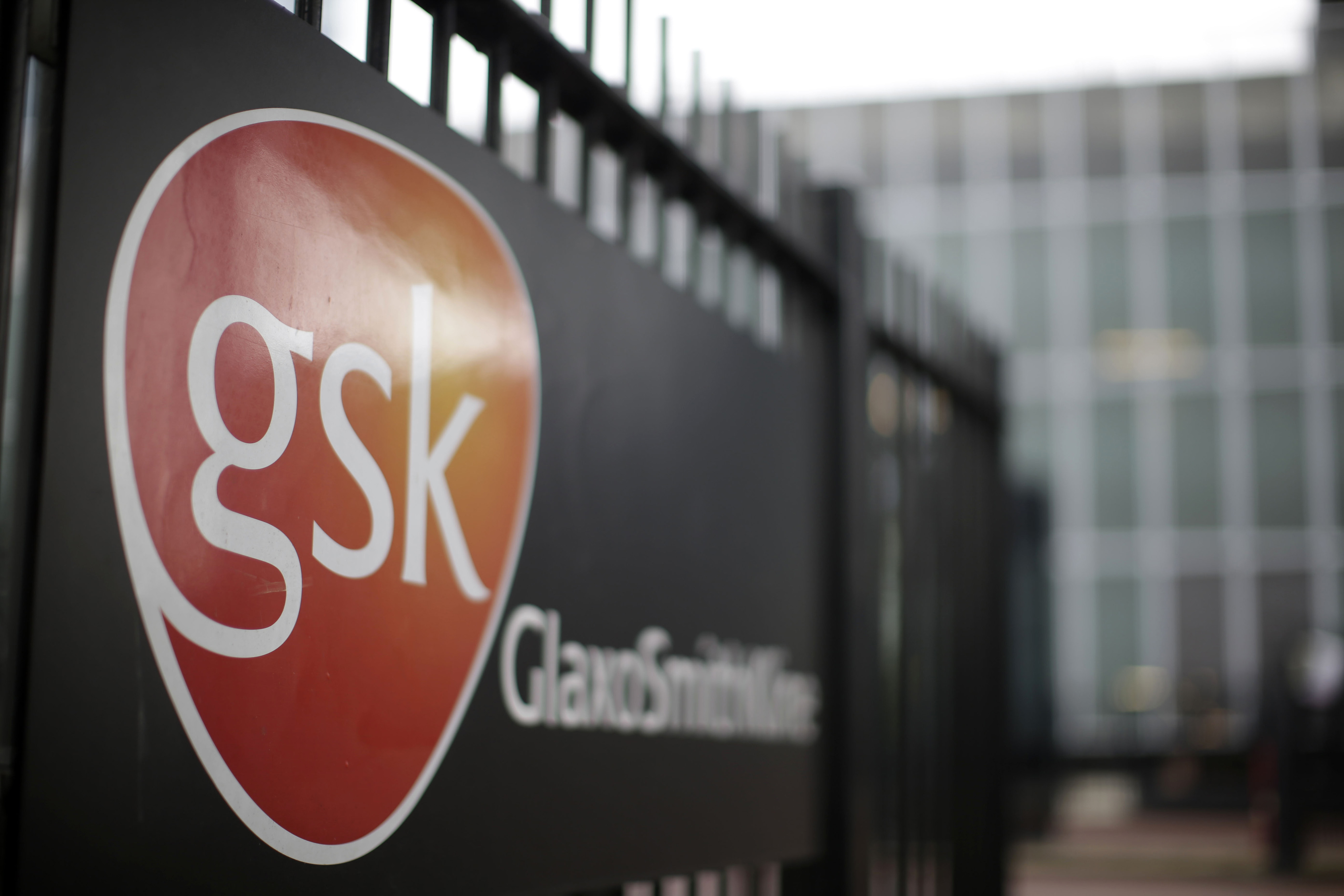The logo of GlaxoSmithKline Plc sits on a sign outside the pharmaceutical company's headquarters in London, U.K., on Tuesday, April 22, 2014.