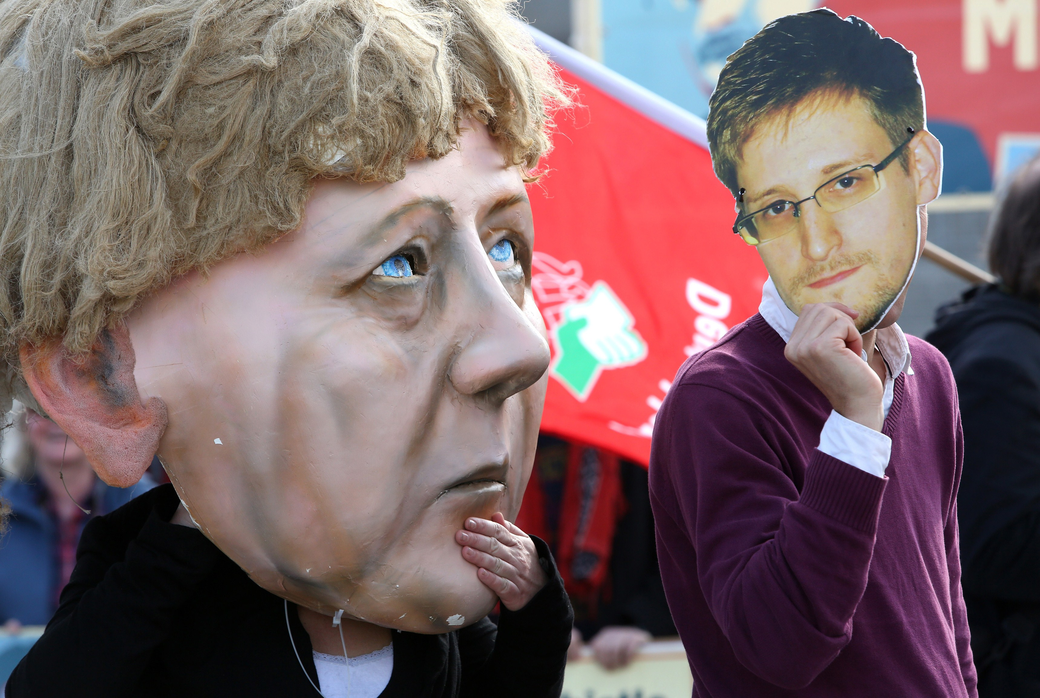 Activists wearing a mask of fugitive U.S. intelligence leaker Edward Snowden (R) and of German Chancellor Angela Merkel take part in a demonstration in favor of an appearance by Snowden as a witness in German NSA hearings held in the German Bundestag, or lower house of parliament, outside the Reichstag building in Berlin on May 8, 2014.