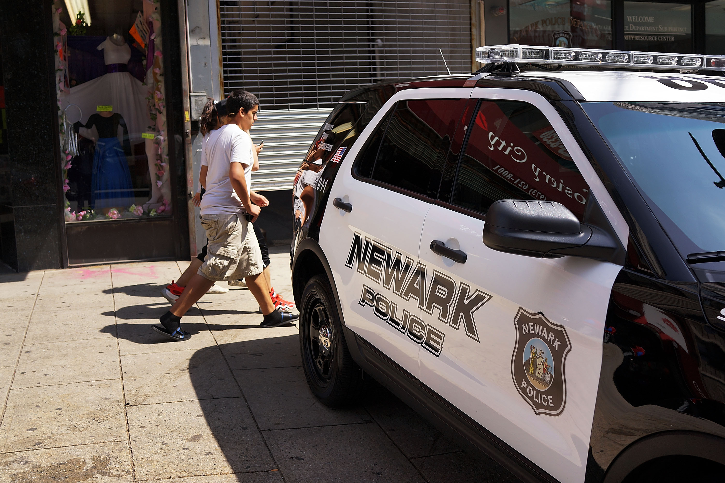People walk by a police car in downtown on May 13, 2014 in Newark, New Jersey.