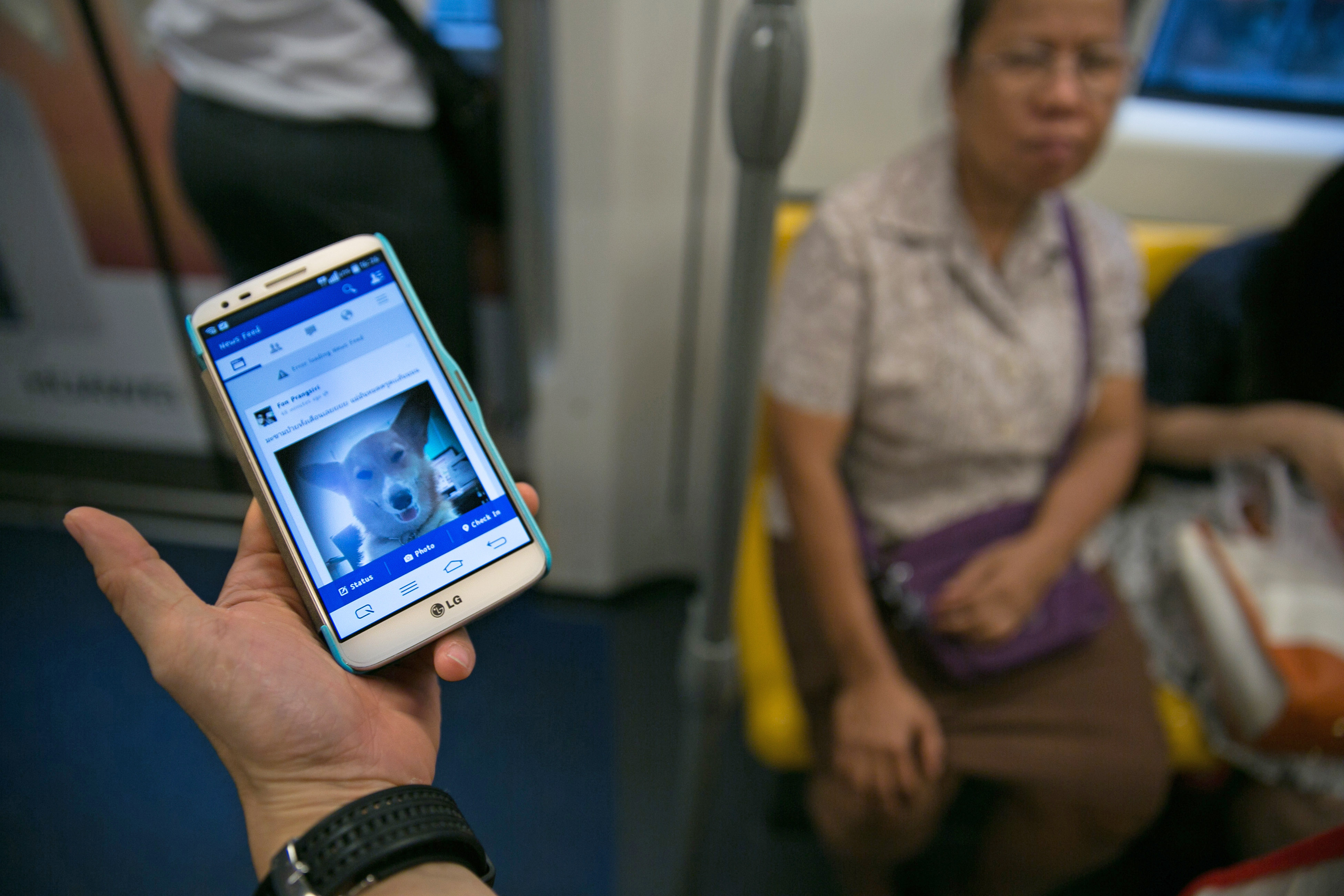 A man shows his mobile phone while riding the Bangkok sky train on May 28, 2014. A widespread Facebook outage occurred in Thailand one afternoon while the ruling military junta who staged a coup denied causing it.