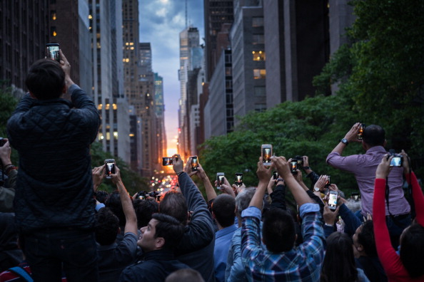 Photographers gather on the Tudor City Place overpass to capture the Manhattenhenge looking across 42nd Street in the Manhattan borough of New York, New York, USA.