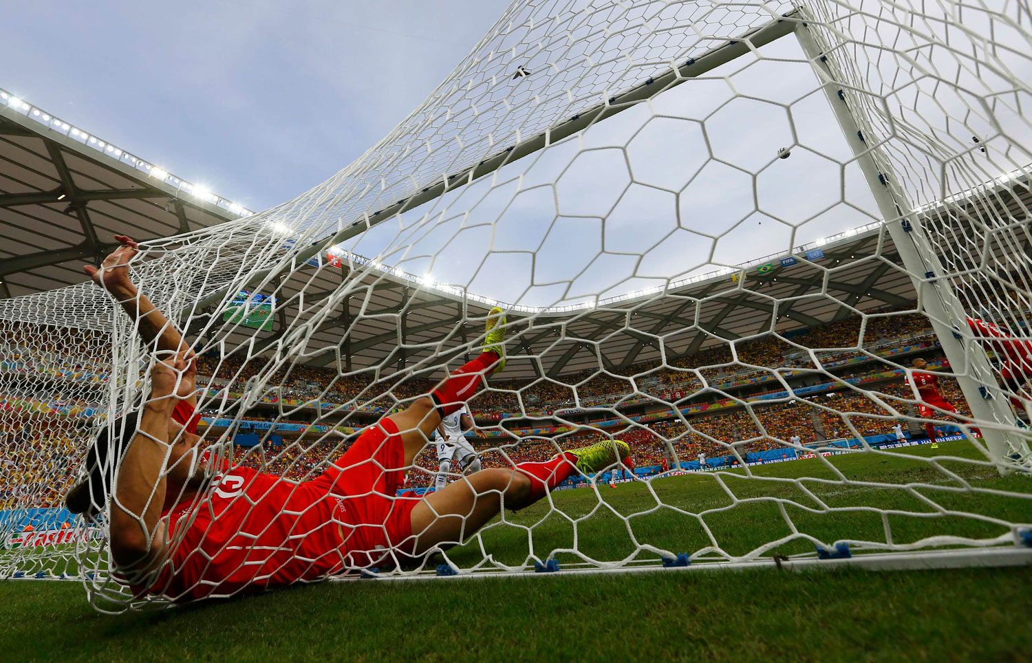 Switzerland's Ricardo Rodriguez falls into the goal net after making a save during their match against Honduras at the Amazonia arena in Manaus, Brazil on June 25, 2014.