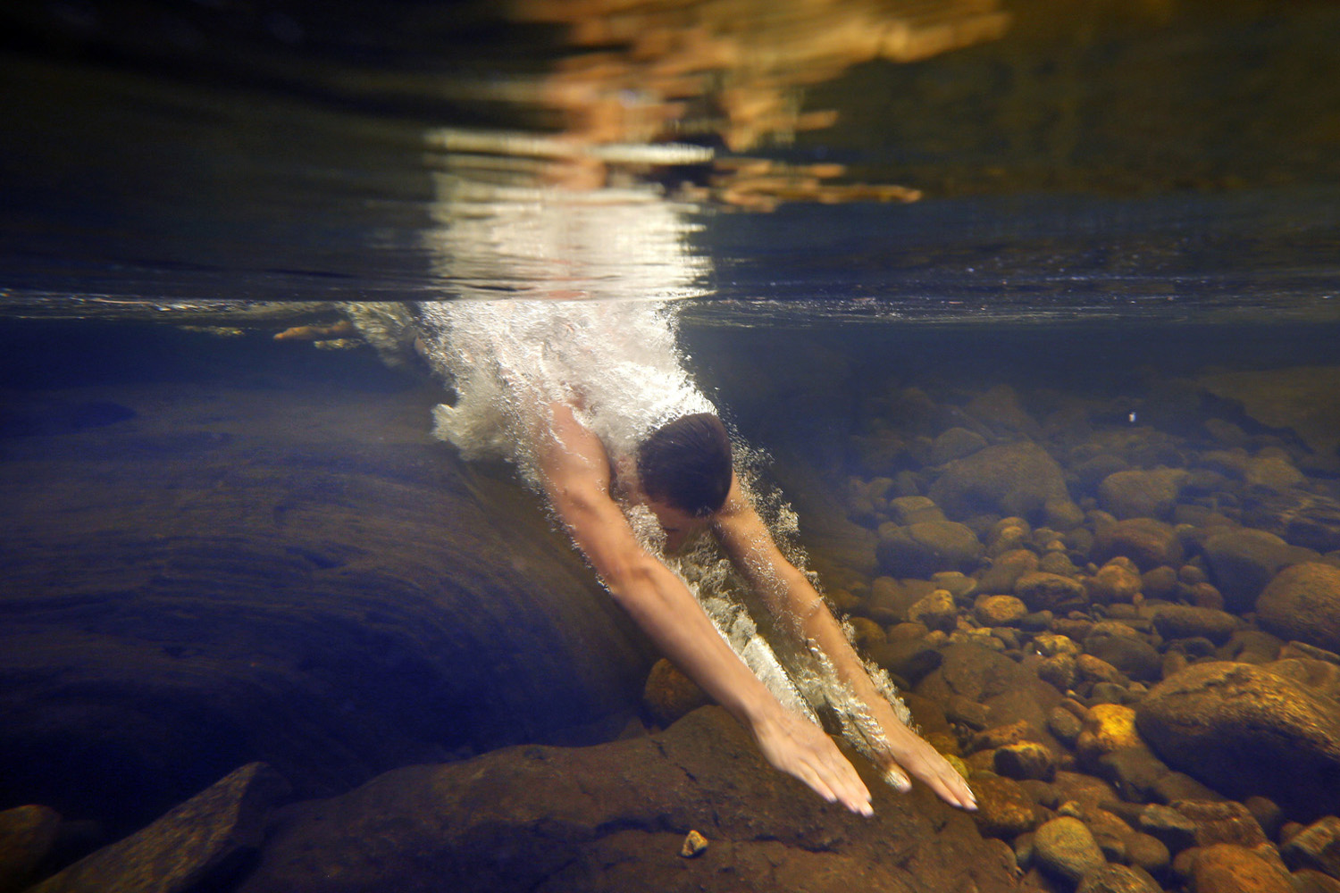 Russell Norris, 15, of Tylertown, Miss., dives into the chilly Swift River at Coos Canyon in Byron, Maine.