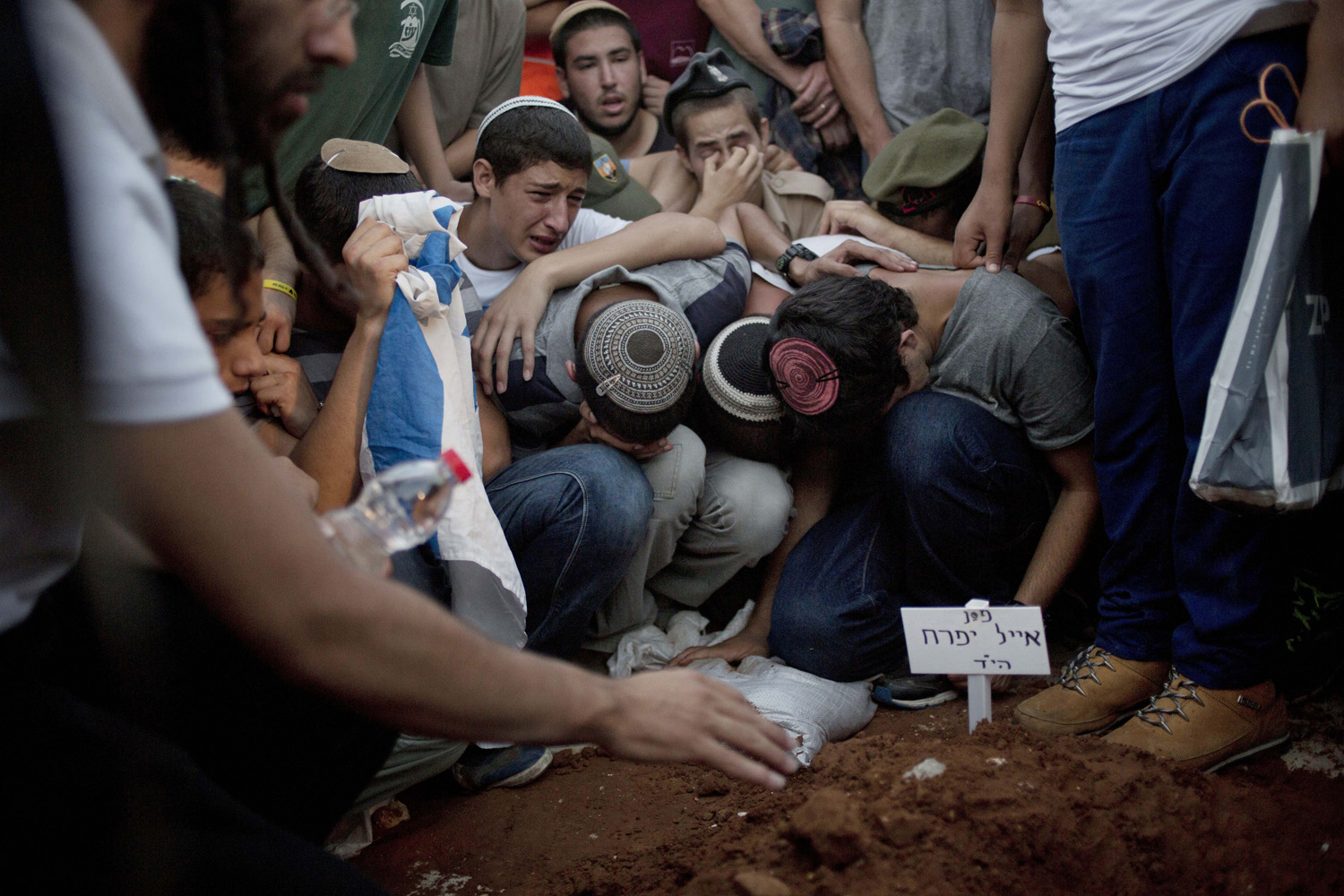 Jul. 1, 2014. Family and friends of Eyal Yifrah, Gilad Shaar, and Naftali Fraenkel , three Israeli teenagers who were abducted over two weeks ago mourn over the grave of  Eyal Yifrah during their funeral in Modiin, Israel.