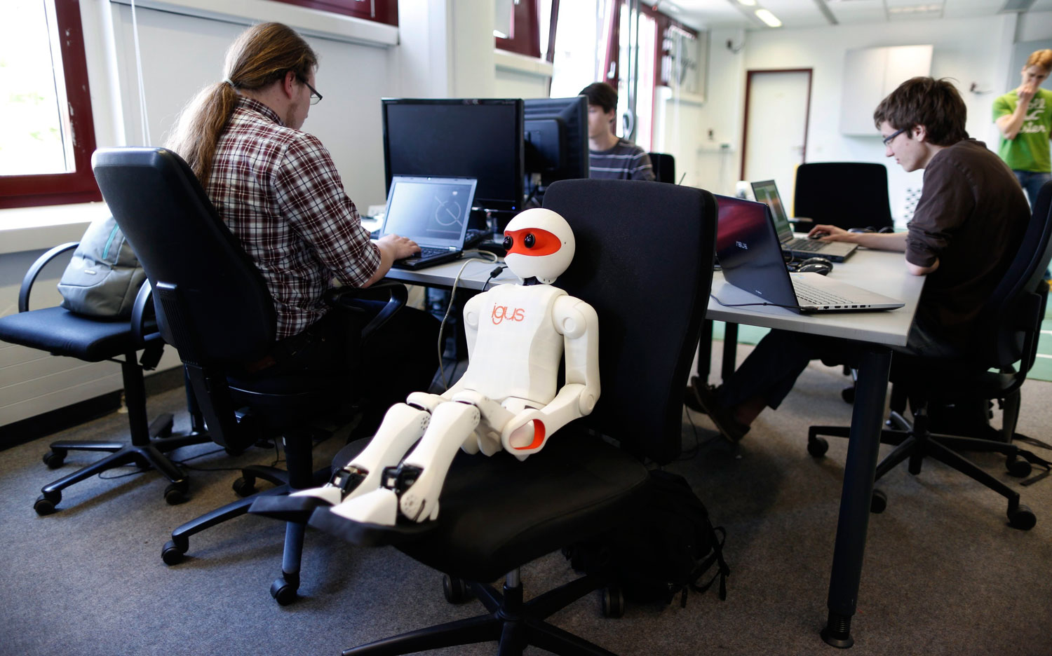 People work on the software of humanoid robots during a photo opportunity at the Institute for Computer Science at the University of Bonn in Bonn, Germany on July 3, 2014.