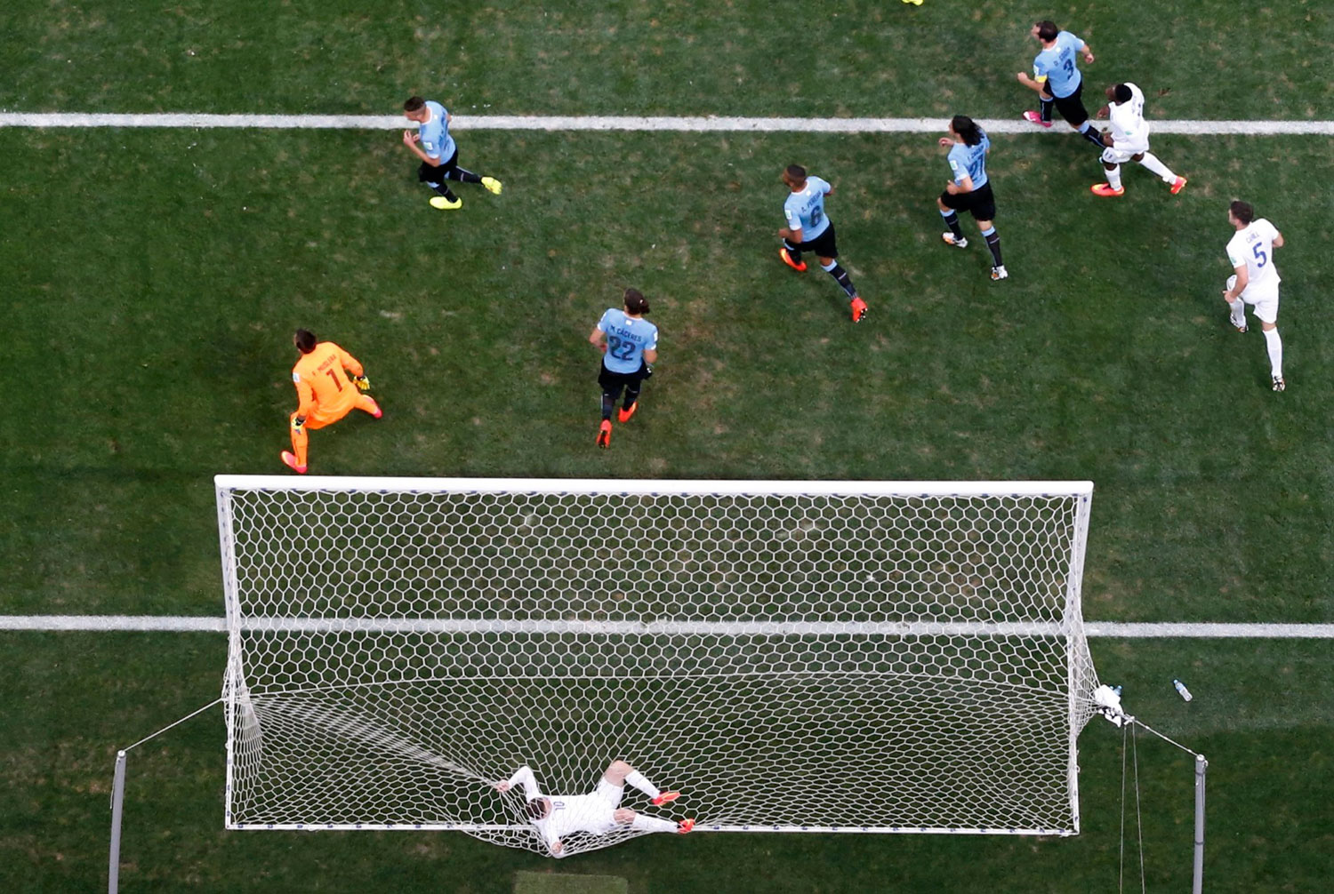 England's Wayne Rooney tangles himself in the net after failing to score a goal against Uruguay during their match at the Corinthians arena in Sao Paulo on June 19, 2014.