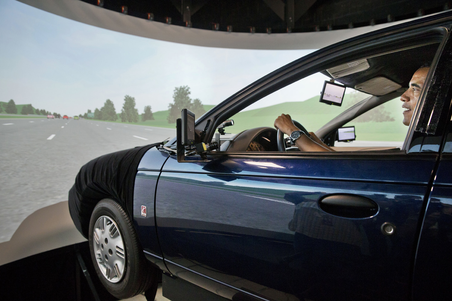 President Barack Obama smiles as he tries out a driving simulation during a tour of the Turner-Fairbank Highway Research Center in McLean, Va. on July 15, 2014.