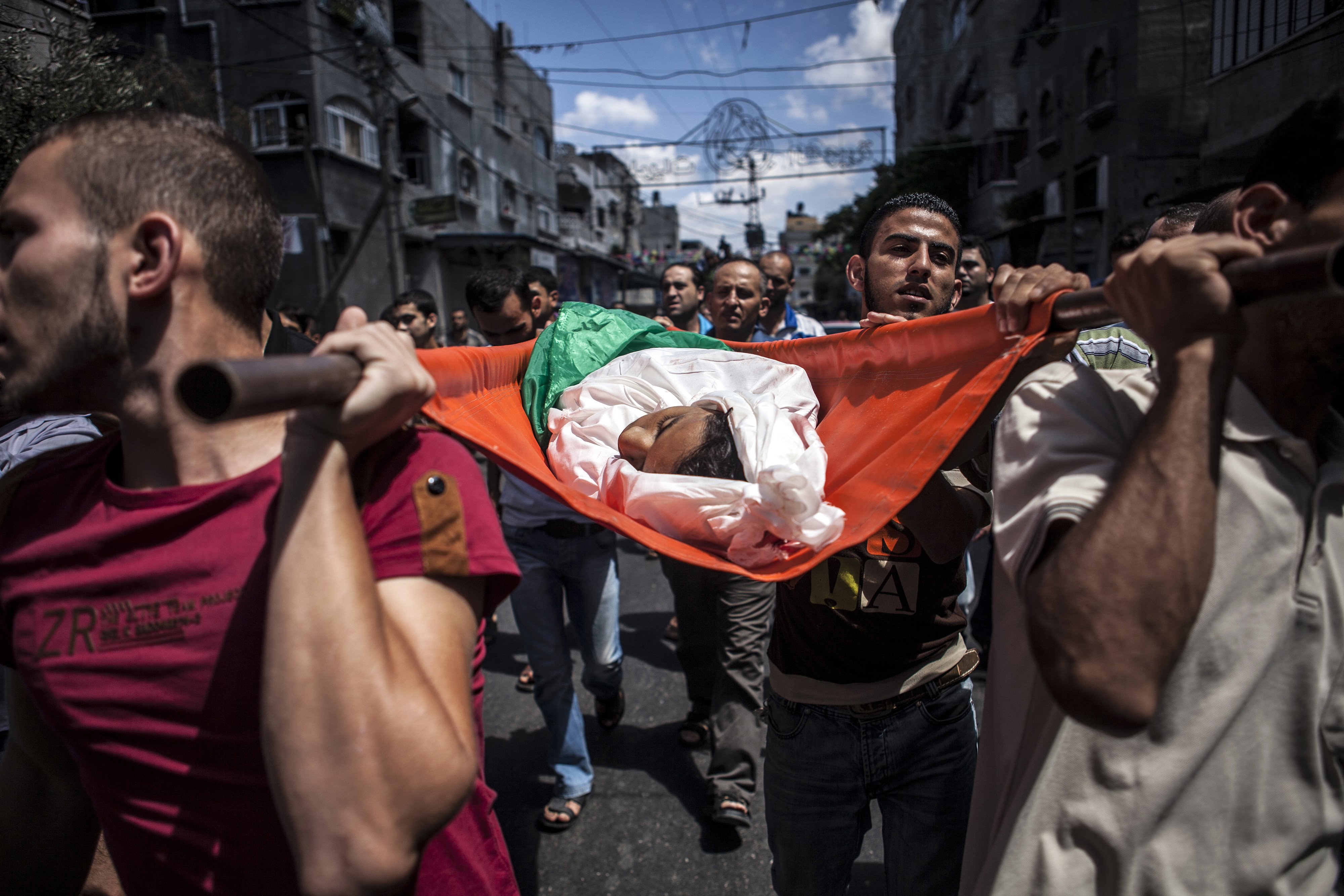 Palestinian mourners gather around the bodies of three siblings of the Abu Musallam family, during their funeral in Beit Lahiya, Gaza Strip on July 18, 2014.