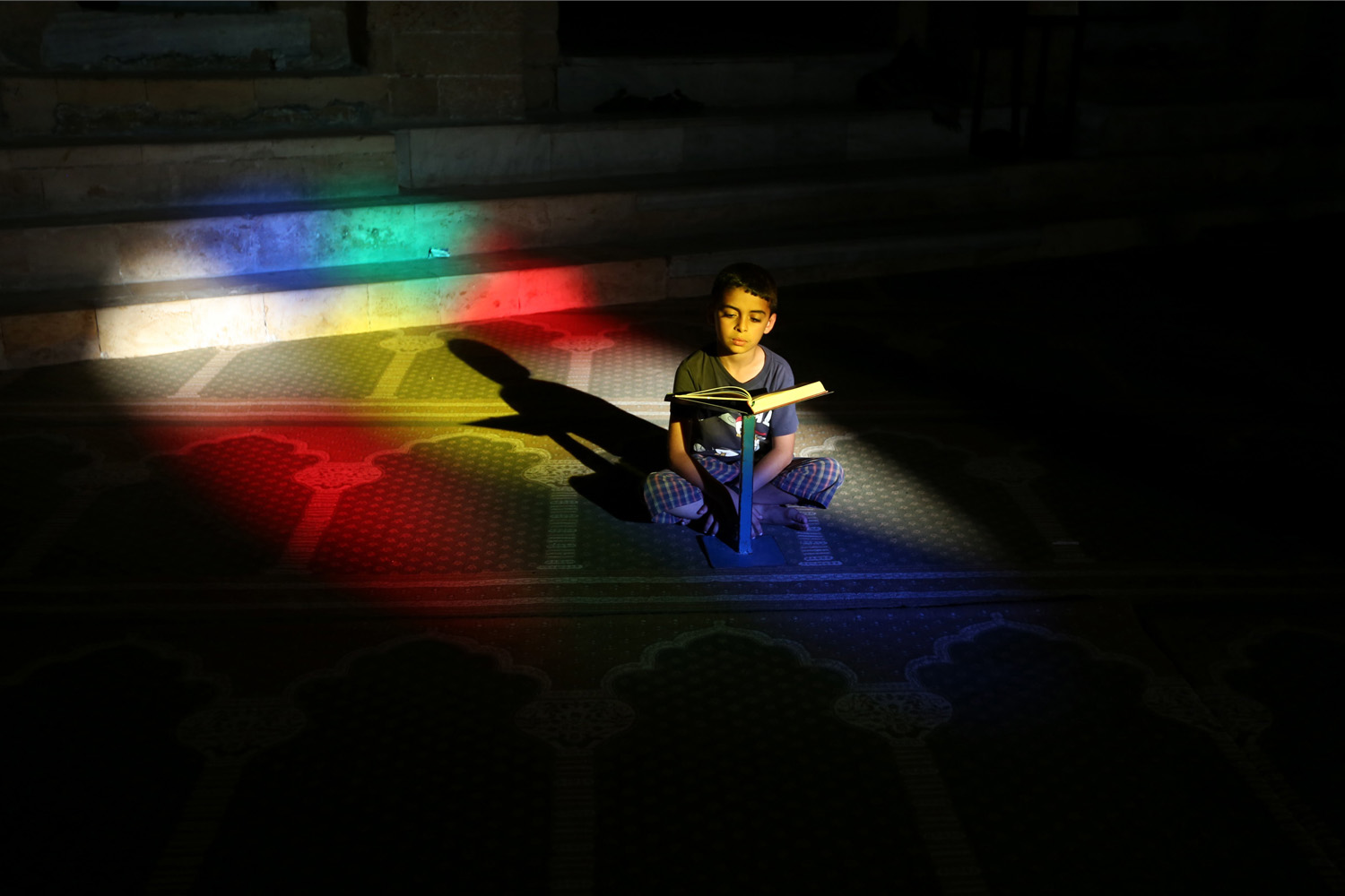 Jun. 29, 2014. A Palestinian boy reads the Quran, Islam's holy book, in the Al-Omari mosque in Gaza City. Muslims throughout the world are celebrating the holy fasting month of Ramadan, refraining from eating, drinking, and smoking from dawn to dusk.