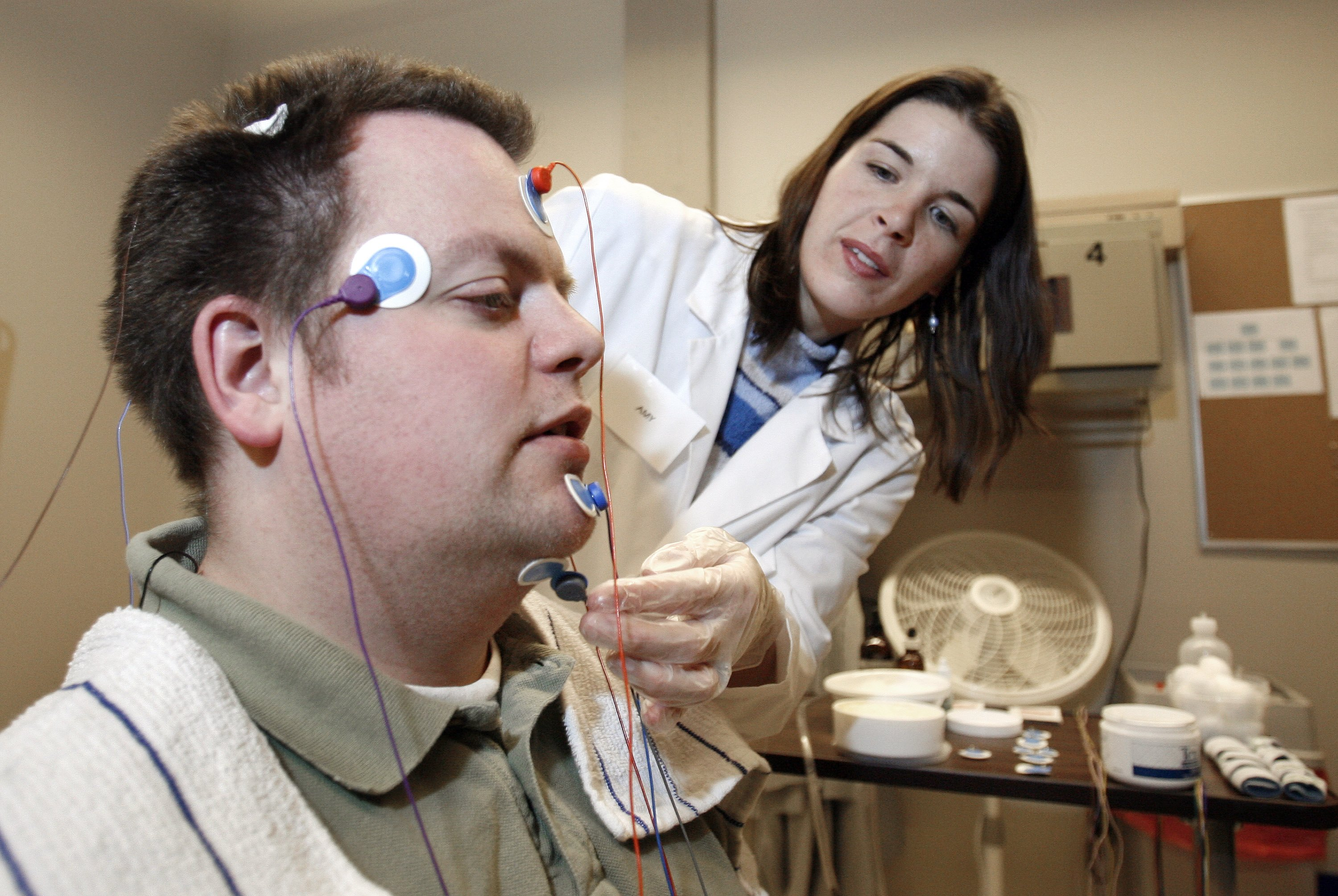 Ryan Gamble has wires applied to his head by lab technologist Amy Bender in preparation for a polysomnographic recording system demonstration at Washington State University Spokane's Sleep and Performance Research Center December 13, 2006 in Spokane, Washington.