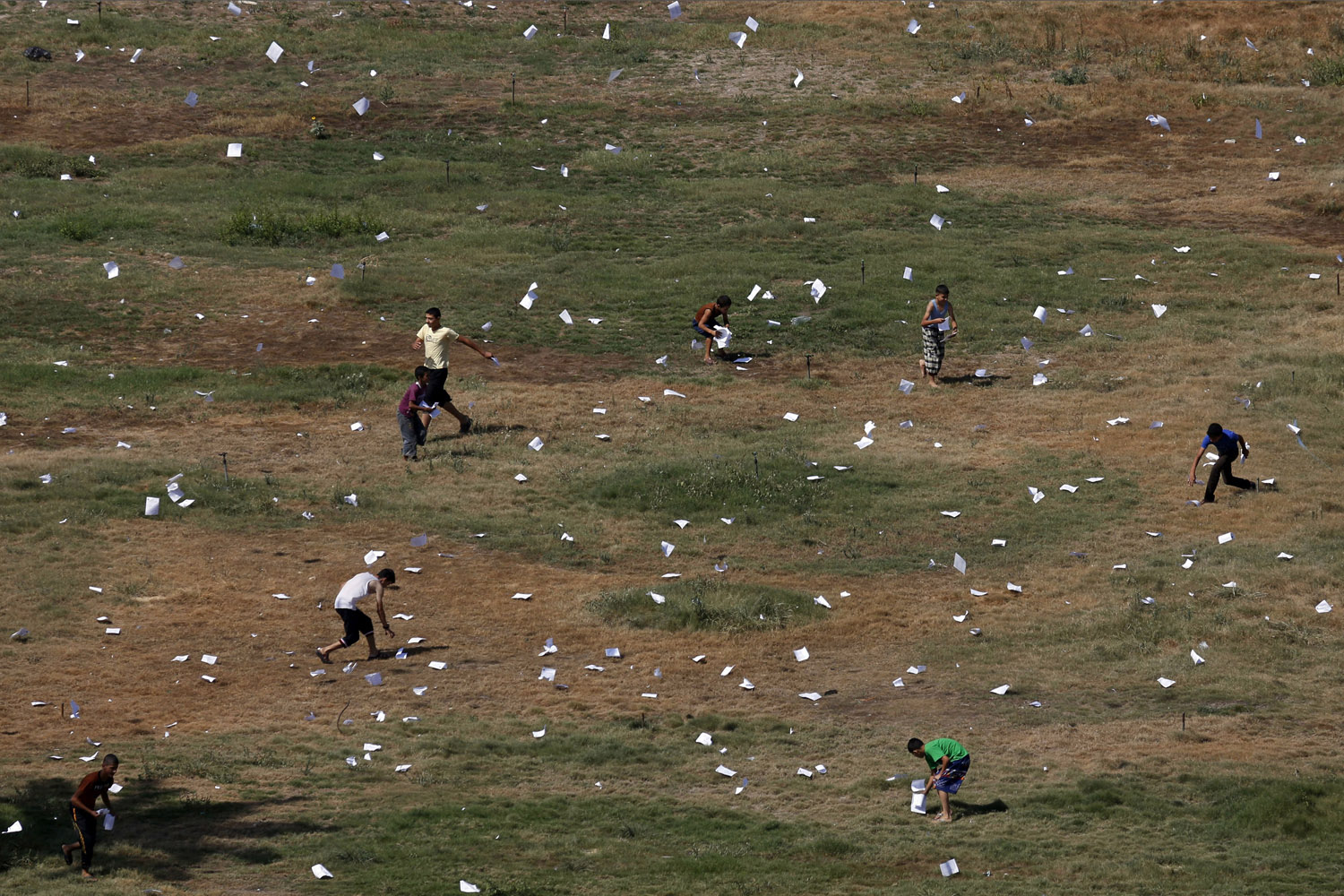 Jul. 30, 2014. Palestinians gather leaflets that fell from an Israeli plane warning residents in Gaza City to stay away from Hamas militants and to report possible rocket launches.