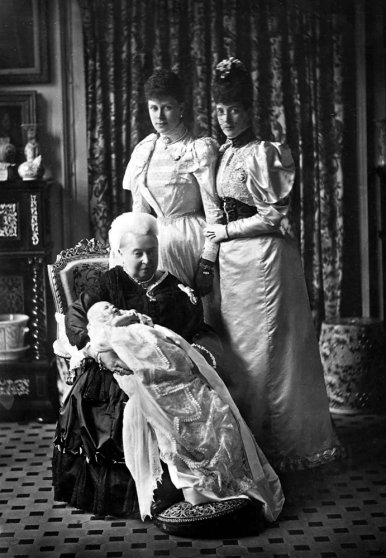 Queen Victoria sits with her grandson the baby Prince Edward (later King Edward VIII) on her knee on his christening while Alexandra and Mary stand behind them. (possibly 1894)
