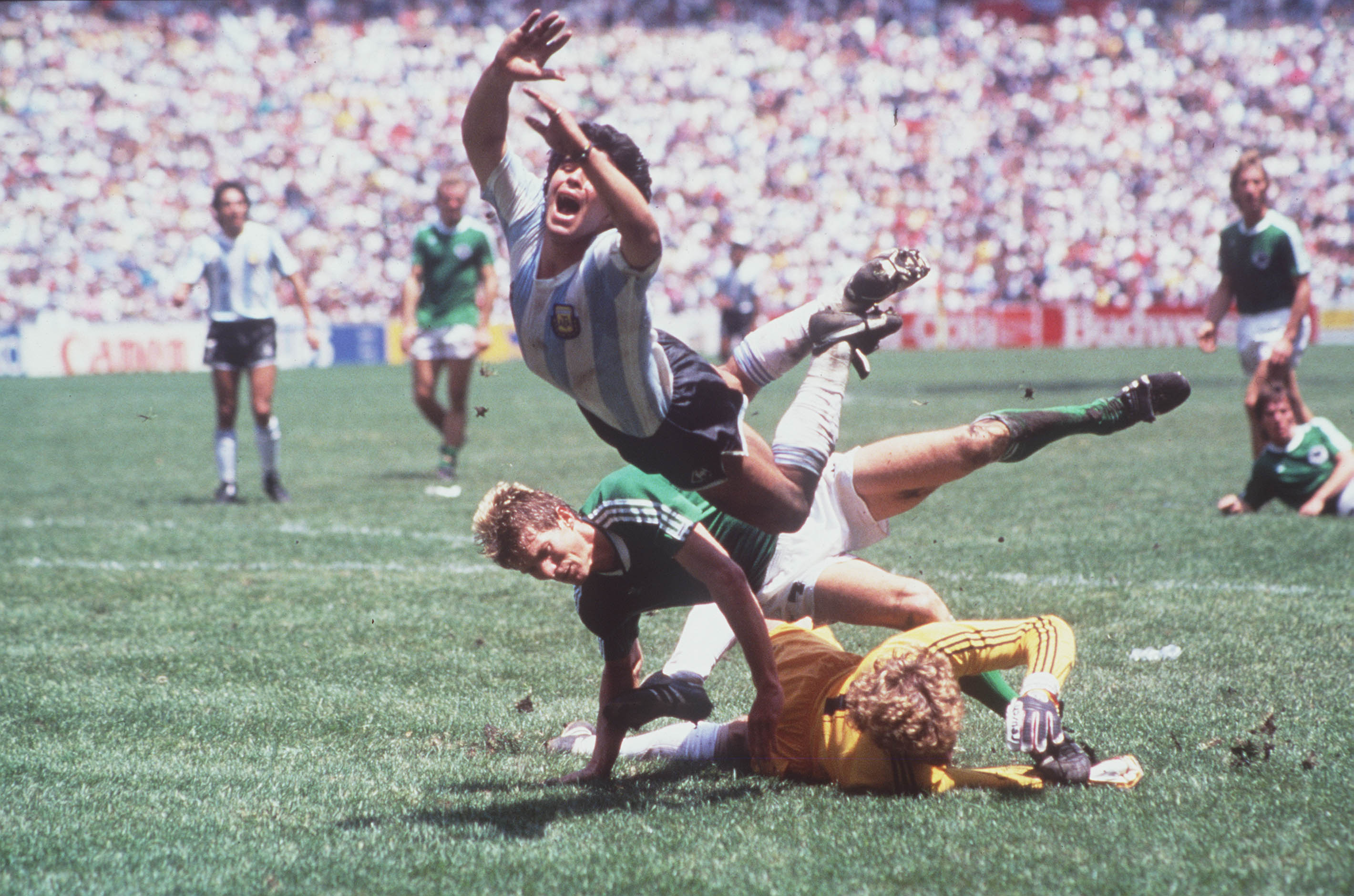 1986 World Cup Final, Azteca Stadium, Mexico, 29th June, 1986, Argentina 3 v West Germany 2, Argentina's Diego Maradona goes flying over the challenges of West German goalkeeper Harald Schumacher and defender Karl Heinz Foerster  (Photo by Bob Thomas/Getty Images)