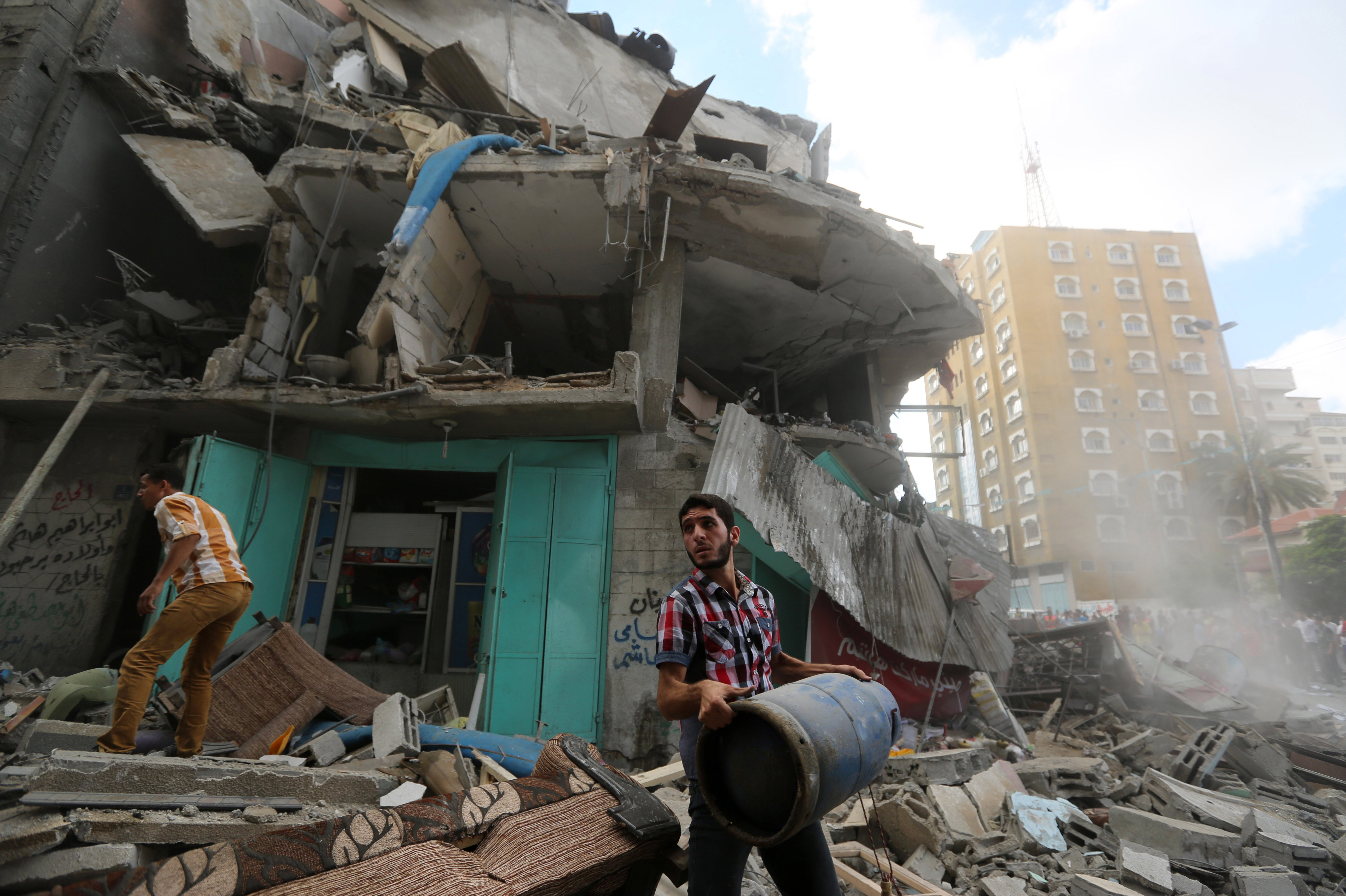 A Palestinian salvages rubble from a destroyed home after an apartment building was hit by an Israeli missile strike in Gaza City on July 18, 2014.