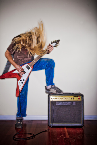 Man thrashes head while playing guitar.