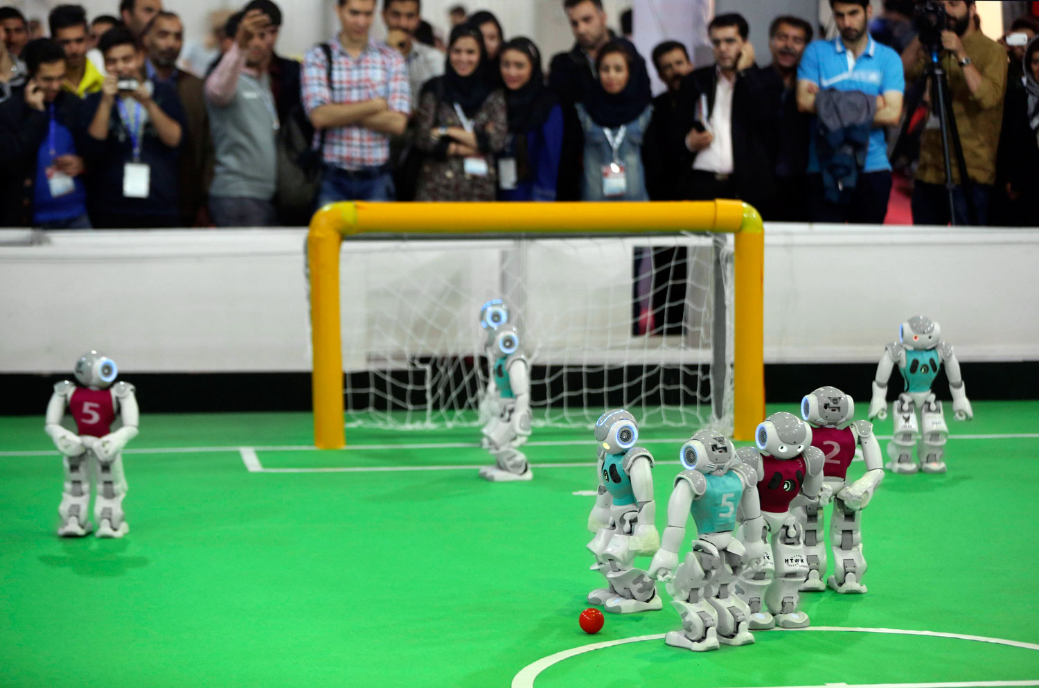 Humanoid robots play during a soccer match while visitors follow the competition in the international robotics competition, RoboCup Iran Open 2014, in Tehran, Iran on April 10, 2014.