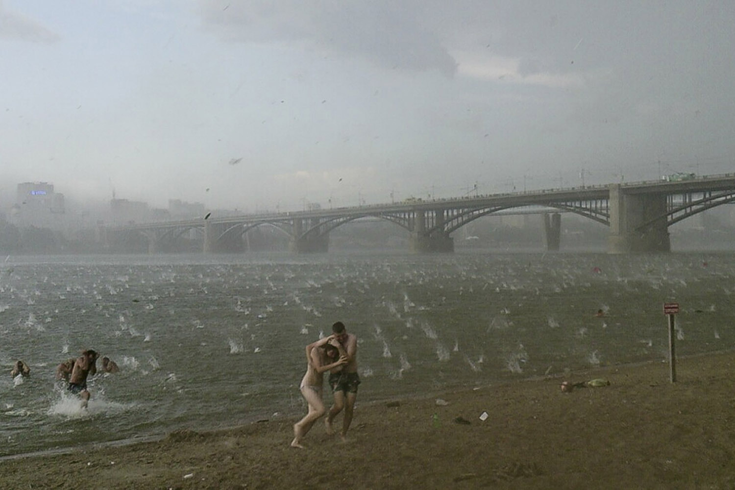 Jul. 12, 2014. People run to shelter from a hailstorm on the beach at Ob River, the major river in western Siberia in Novosibirsk, Russia.