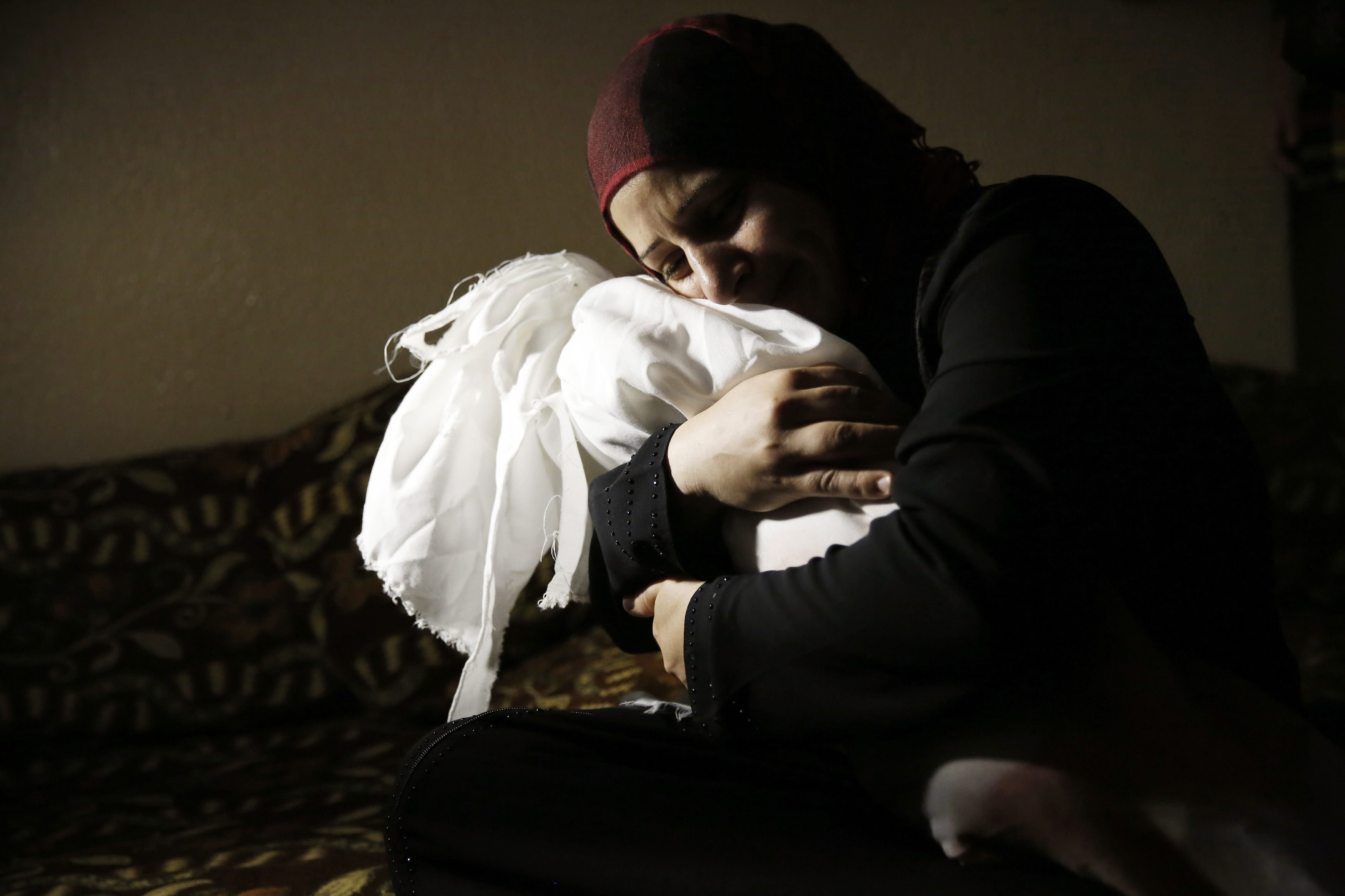 Netream Netzleam holds the body of her daughter Razel, 1, who died in an Israeli air strike on Thursday afternoon, at her funeral in Rafah in the southern Gaza Strip on July 18, 2014.