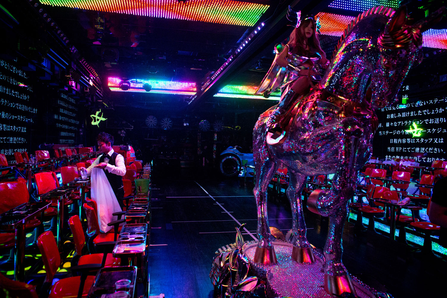 A man cleans up the stage after a show as a large robotic horse is moved back into position after a show at The Robot Restaurant on June 29, 2014 in Tokyo.