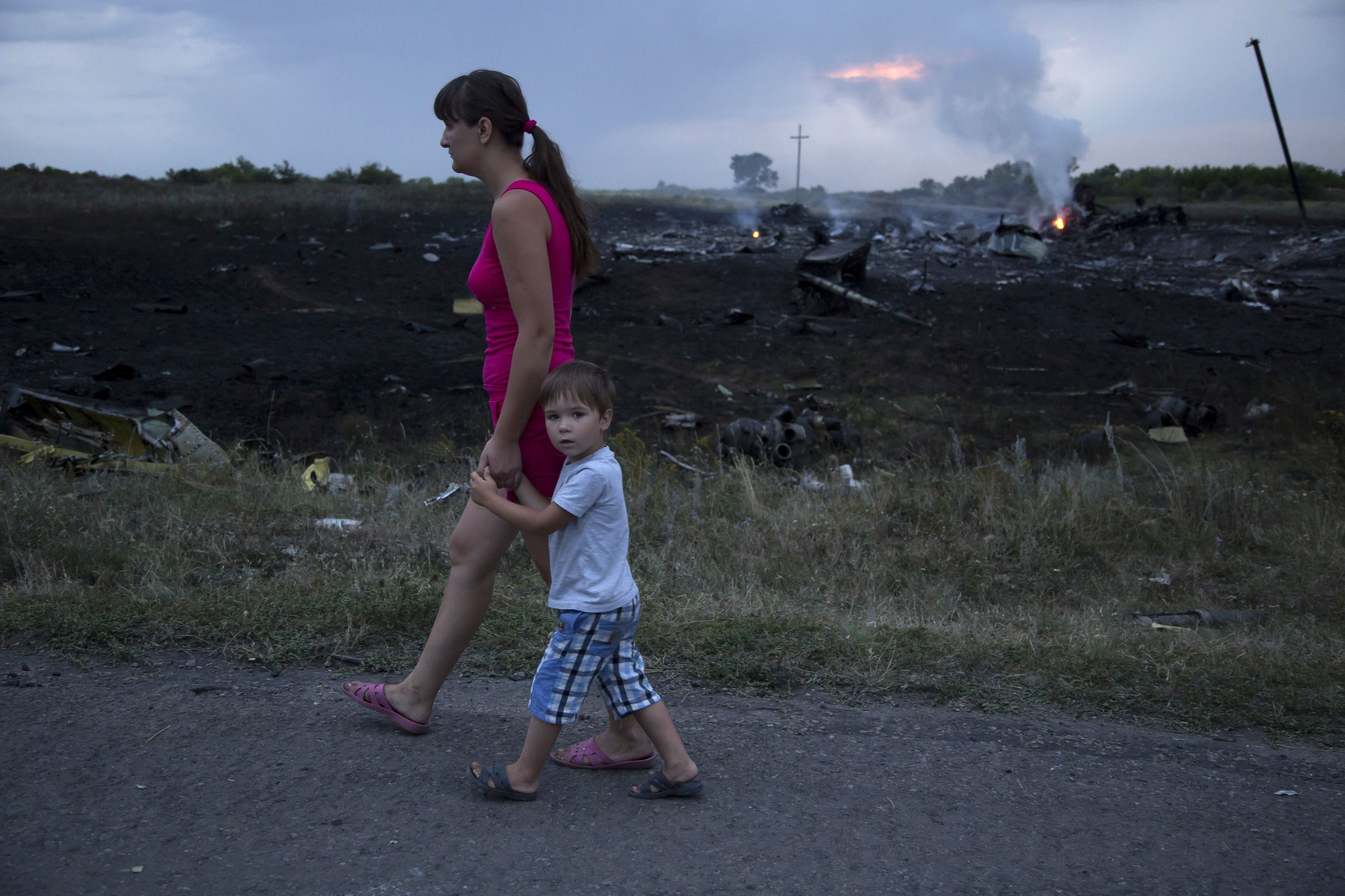 A woman and child walk past the crash site of a passenger plane near the village of Grabovo, Ukraine, July 17, 2014.