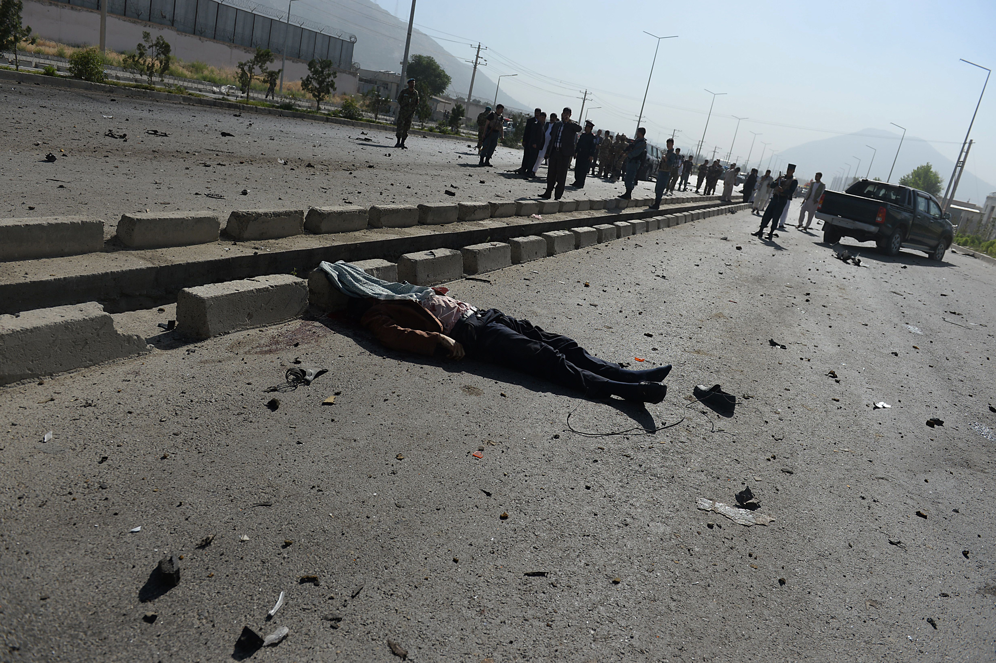 A victim's body lies on the road as Afghan security forces inspect the site of a suicide attack in Kabul on June 21, 2014.