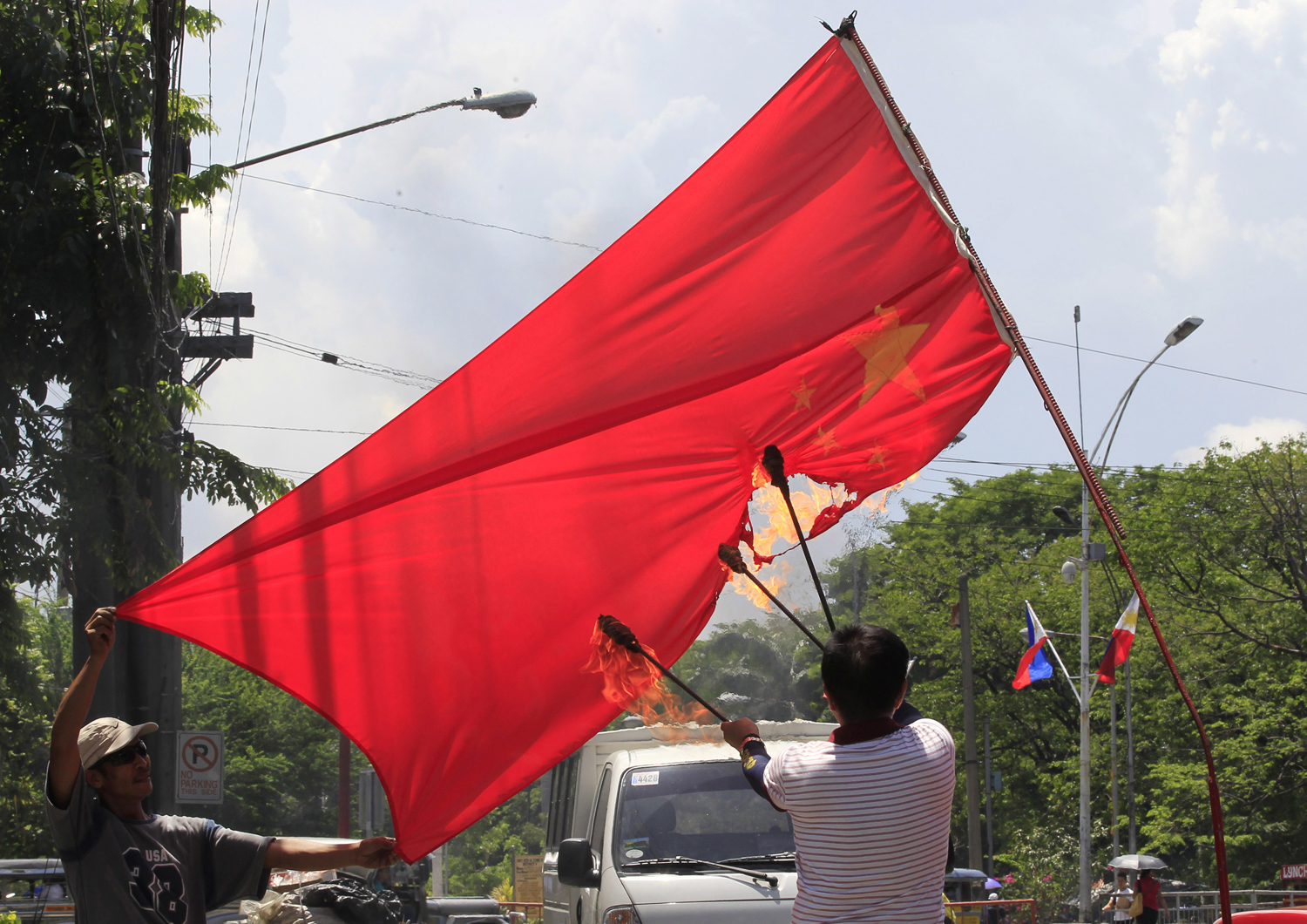 Abner Afuang, a retired policeman, sets fire to an inverted Chinese national flag during a protest in Manila on June 9, 2014.